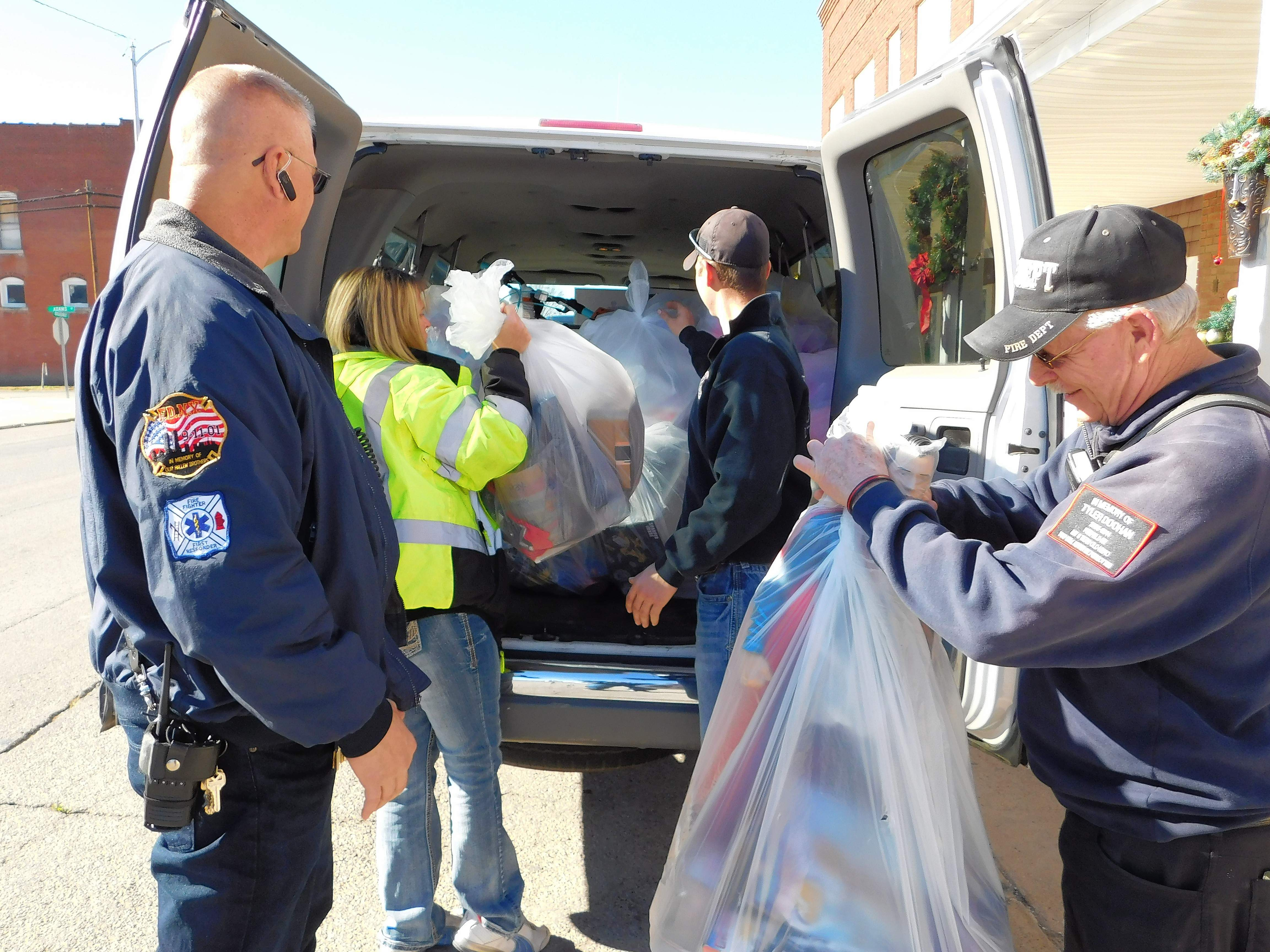 Assistant Fire Chief Greg Jennings, left, and volunteers Tricia Smith, Wayne Rice and Mike Teeling drop off $2,300 in gifts Saturday at Johnston City's Manna Mission.
