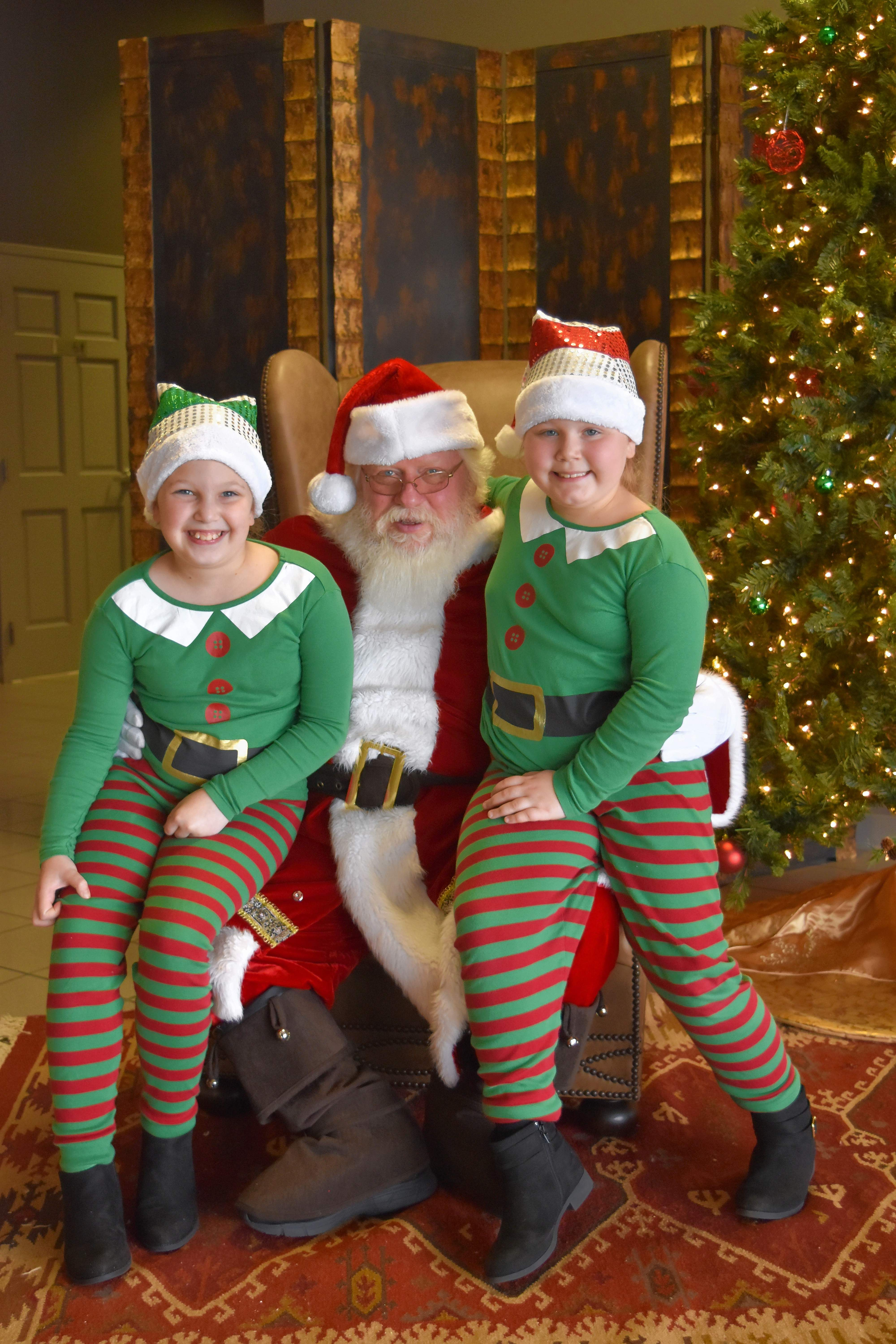 Santa Claus visited Harrisburg Saturday morning at the Bonan Business Center, along with two of his elves, Klaire Stich, left, and Adi Stich of Wayne City.