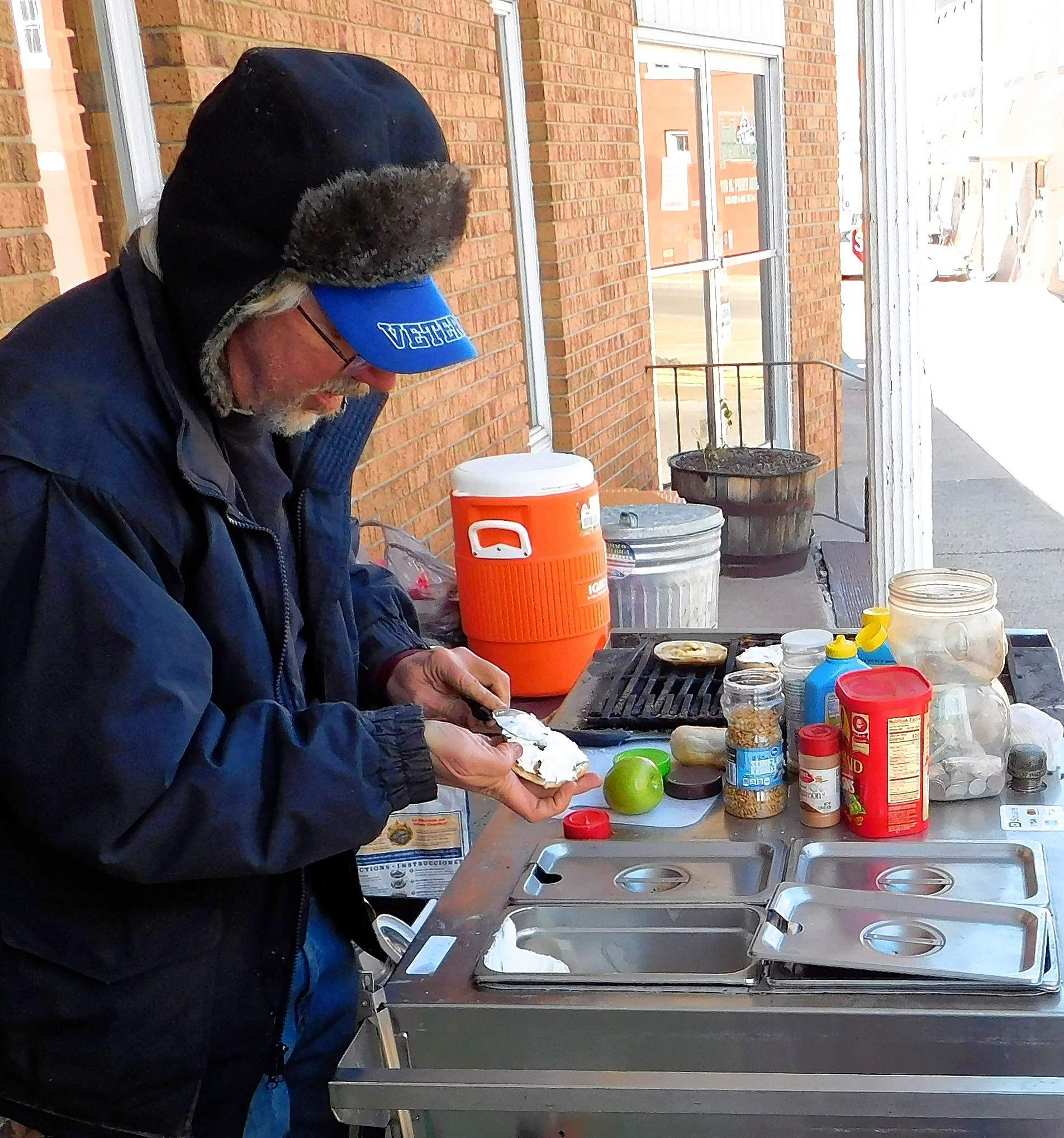 Brad Preiss, or B-Rad, as he prefers to be known, prepares a warm bagel for one of several customers that that trickled in for a treat Thursday. Preiss was set up outside of Marion's Hill Printing at the invitation of owners Rita and Earl Sigley.