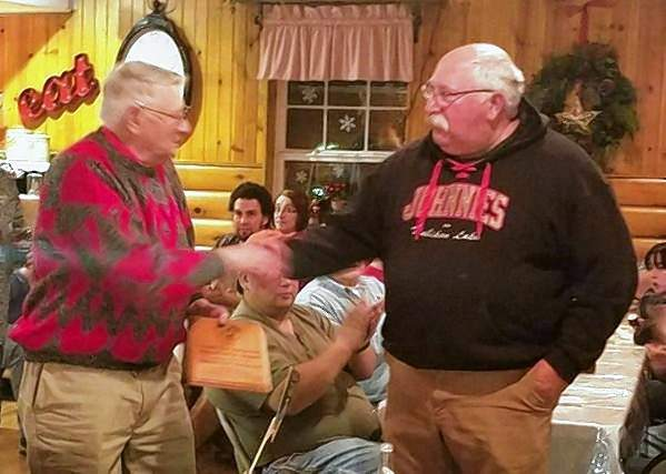 Lowell W. Patterson of Harrisburg (left) accepts a plaque from John Aschenbrenner, president of the 100 Mile Nicolet Snow Safari Snowmobile Club during a club meeting last month. The plaque commemorates that a newly established humanitarian award has been named in honor of Patterson.