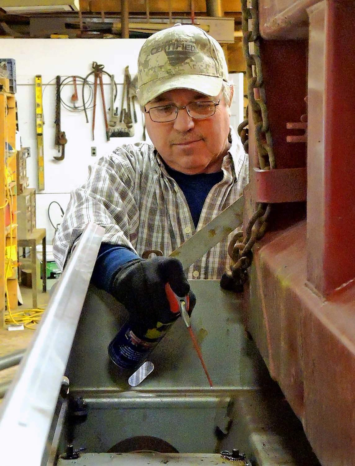 Saline County Highway Department maintenance worker Greg Cowger lubricates a tailgate spreader in preparation for the snow expected to begin late Thursday evening.  Most of the county's snow plow fleet has been ready for action for more than a month.