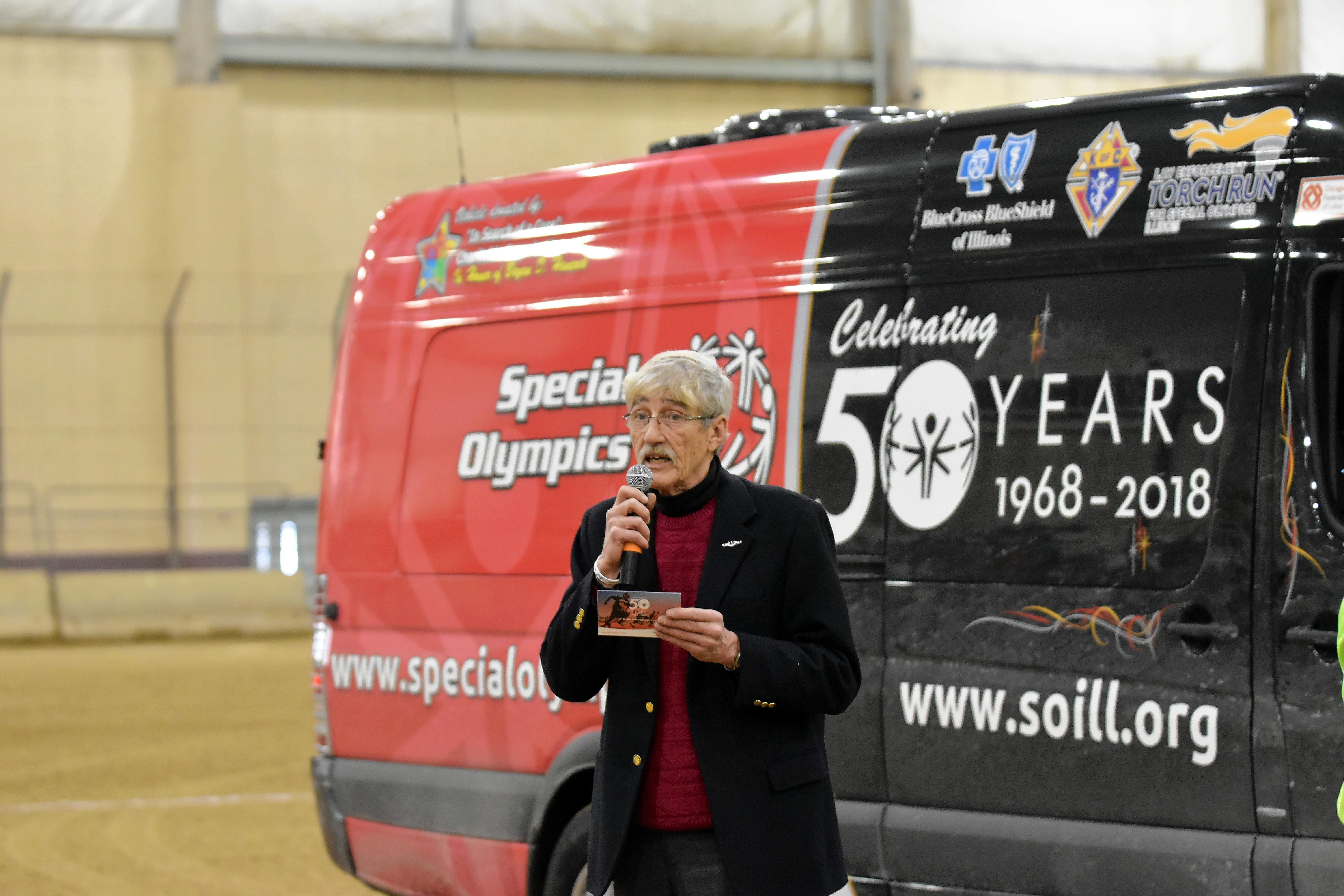 Hiram Brownell, Special Olympics historian, speaks during the opening ceremony. Brownell is traveling across the state in the van behind him as part of the lead-in to July's start of the year-long observation of the 50th anniversary of the Special Olympics.