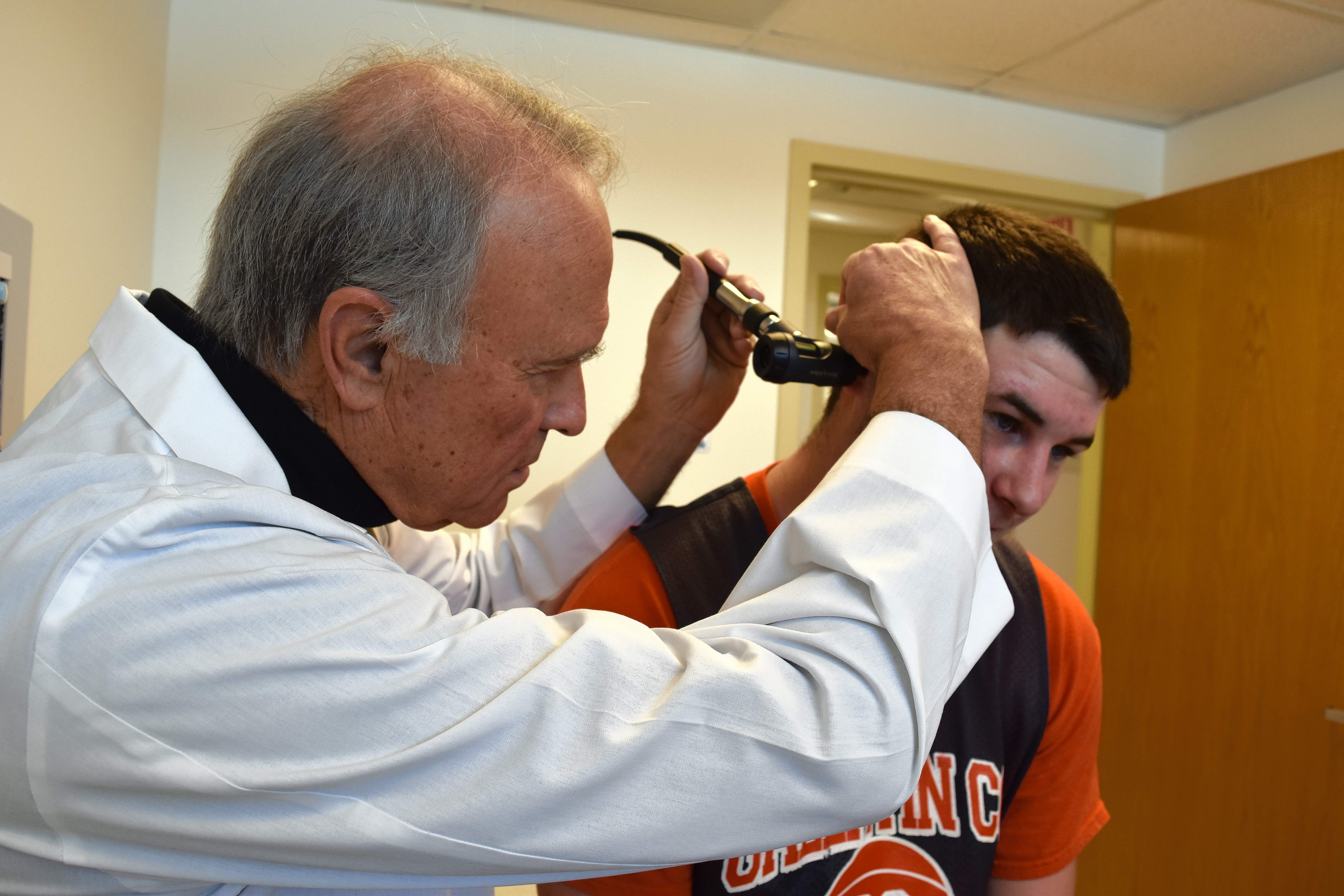 Dr. Tom Martin gives a demonstration of an ear exam at the Gallatin County Wellness Center. The clinic, attached to the west side of Gallatin County High School, is available for patients who need to see a doctor.