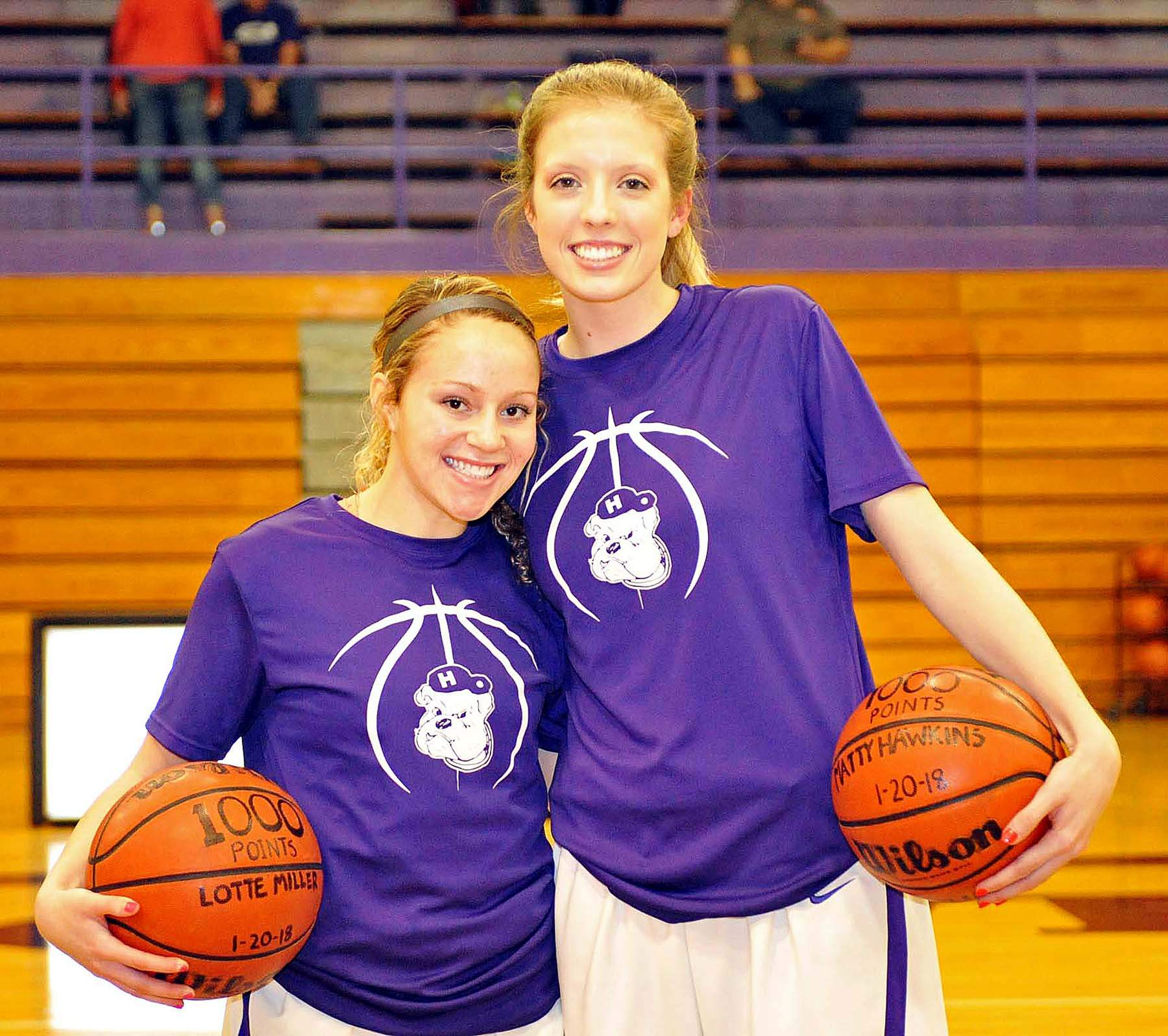 Lotte Miller (left) and Matty Hawkins (right) each surpassed 1,000 career points recently and were presented game balls Tuesday evening before their game with Massac County at Davenport Gym in Harrisburg.