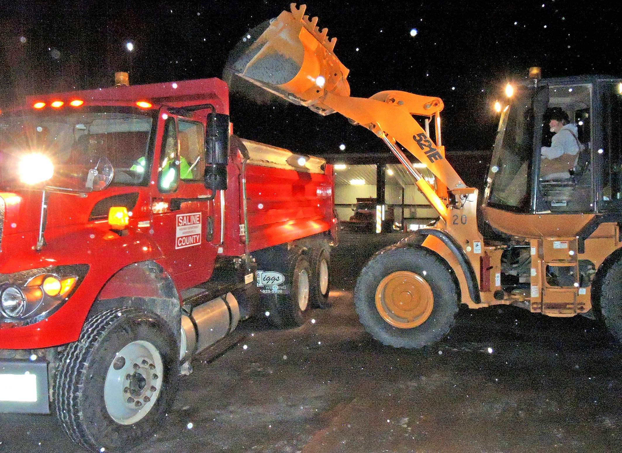 Saline County Highway Department foreman Richard Simpson loads salt onto a truck driven by fellow employee Todd Church Tuesday night at the department's stockpile. The salt was applied to the most hazardous locations, including College Road and Harco Road in anticipation of freezing rain throughout the night.
