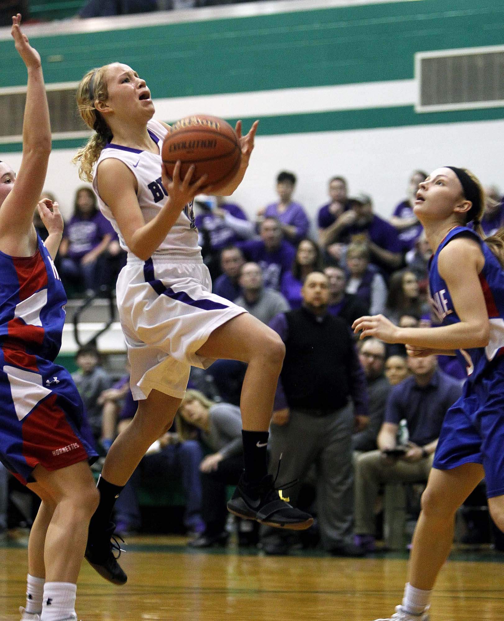 Harrisburg senior point guard Lotte Miller splits the Nashville defense for two of her game-high 17 points in Tuesday night's 43-30 IHSA Class 2A Sectional semifinal win at Hamilton County High School.