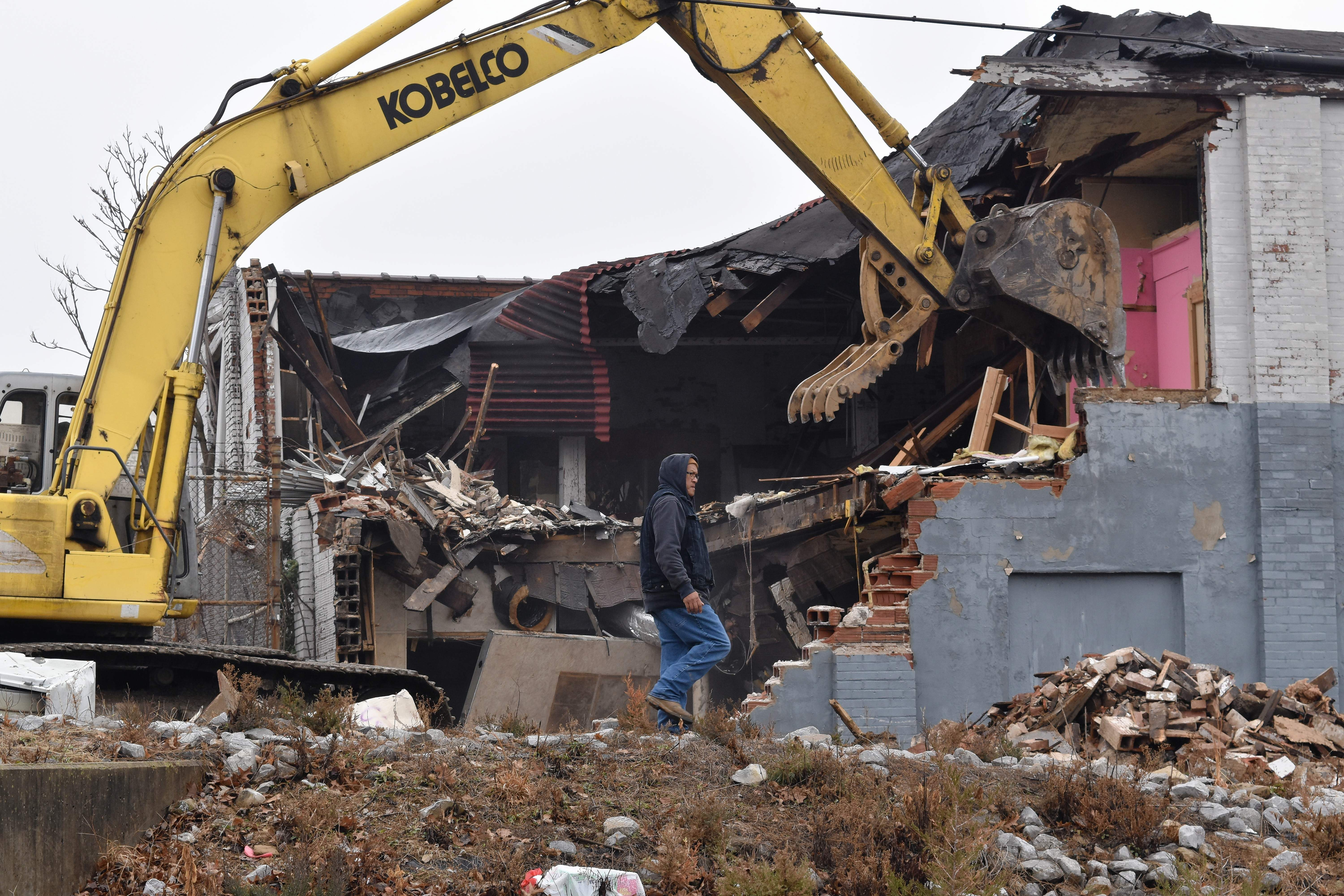 A demolition worker moves his position as another worker using a trackhoe tears down a brick building on Jackson Street in Harrisburg. This is part of the city's ongoing project to renovate properties within the city.