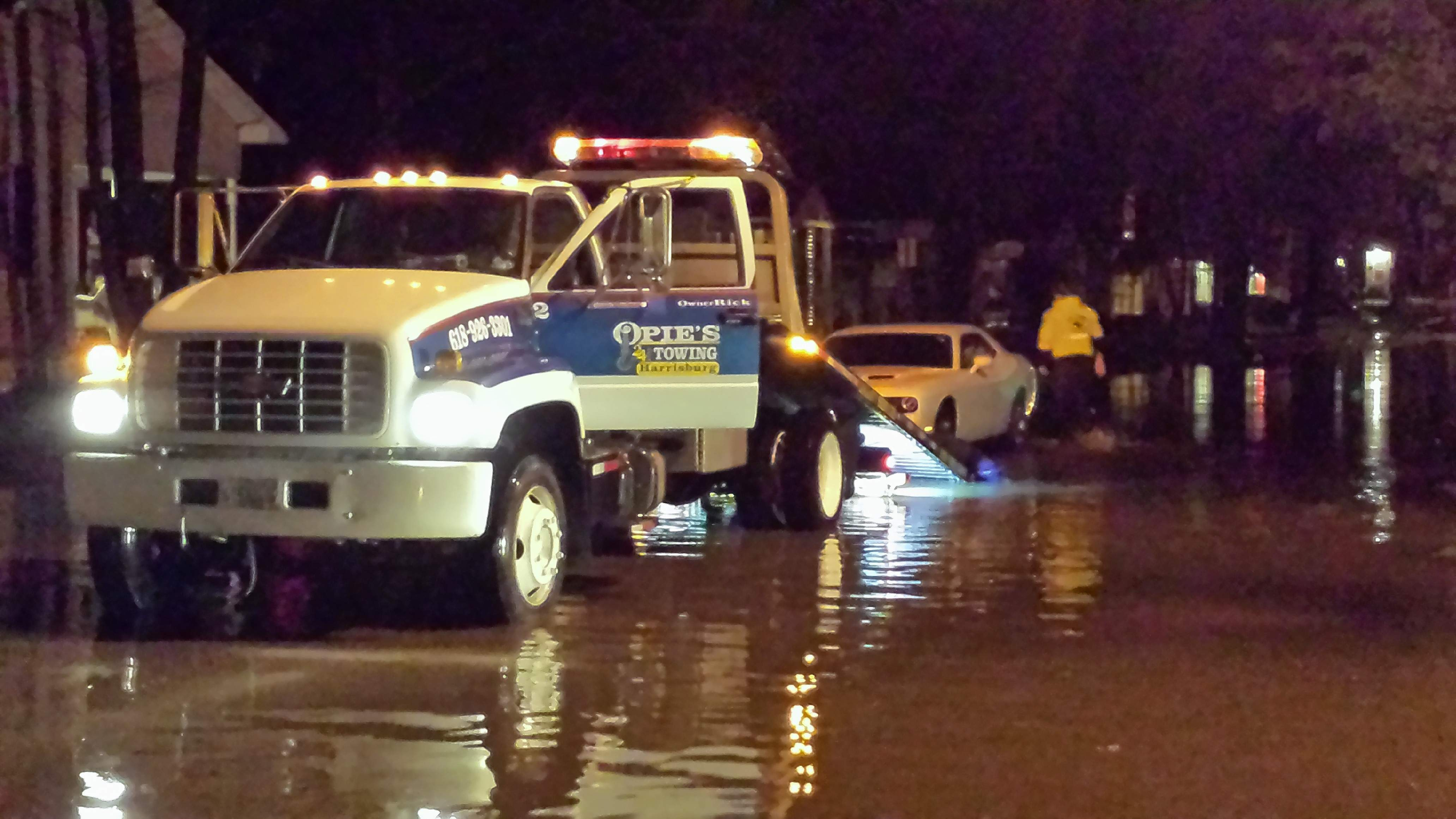 Opie's Towing of Harrisburg prepares to pull a stalled car from floodwaters on South Main Street Saturday night.
