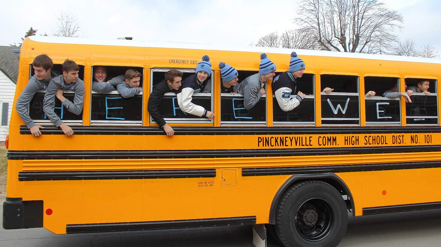 The Panthers lean out the windows as students and staff cheer.