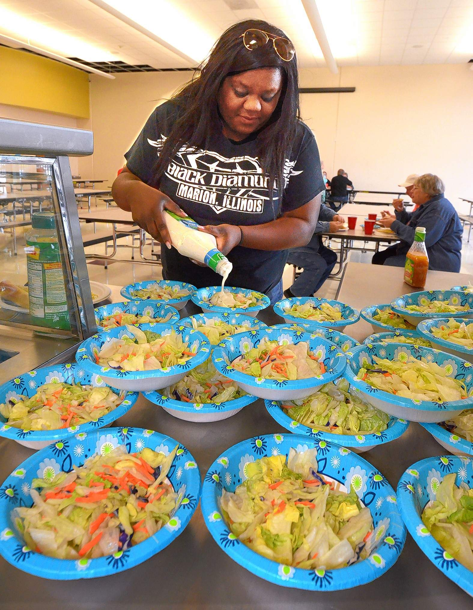 Dana Felts added dressing to her salad Saturday evening at Adams Grade School during the Creal Springs Park District's spaghetti fundraiser benefiting the community's annual Wonder Water Reunion.