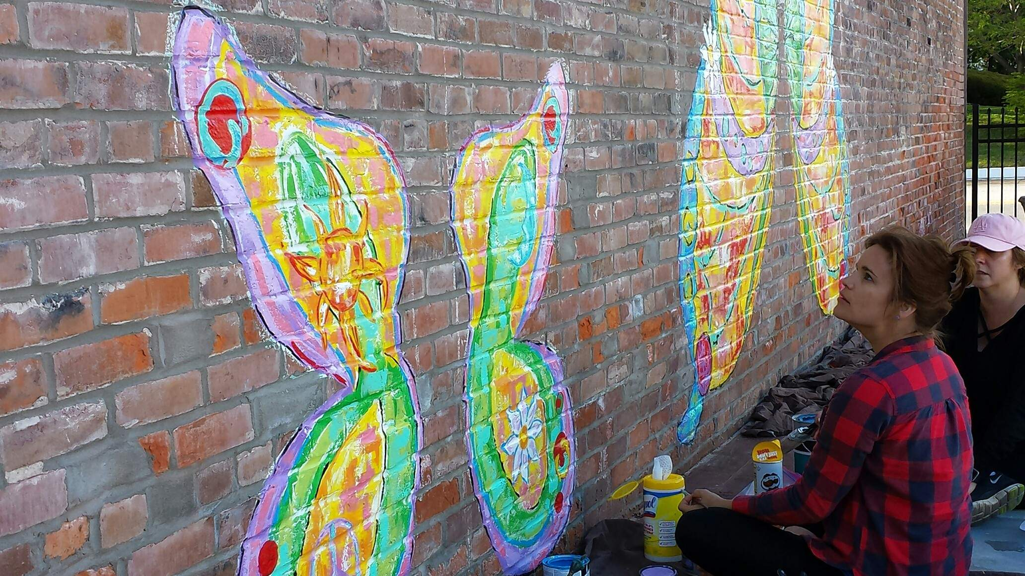 Harrisburg artist Hayley Kotner, left,, along with friend Tammi Jackson, work on adding details to a set of butterfly wings Kotner has painted on the east side of the Towne Square Pub in Harrisburg.