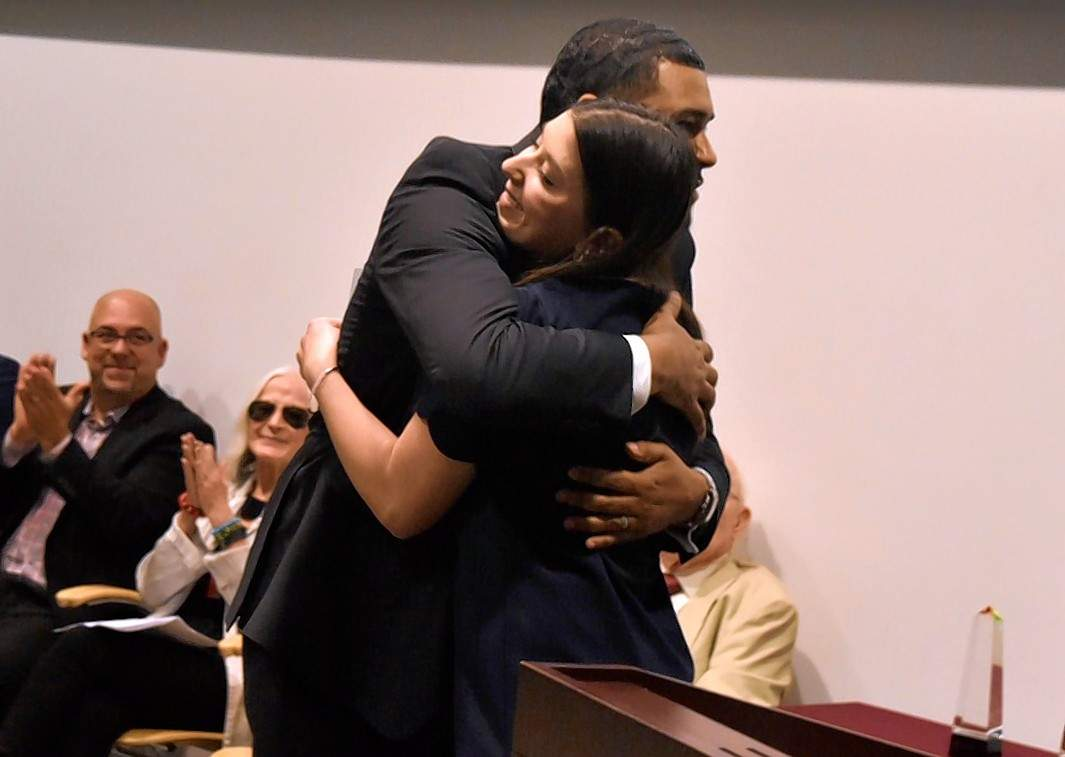 Geoffrey Ritter photoBooth shares a hug with former student Danielle Lorentz, who introduced him at Friday's ceremony at Morris Library.