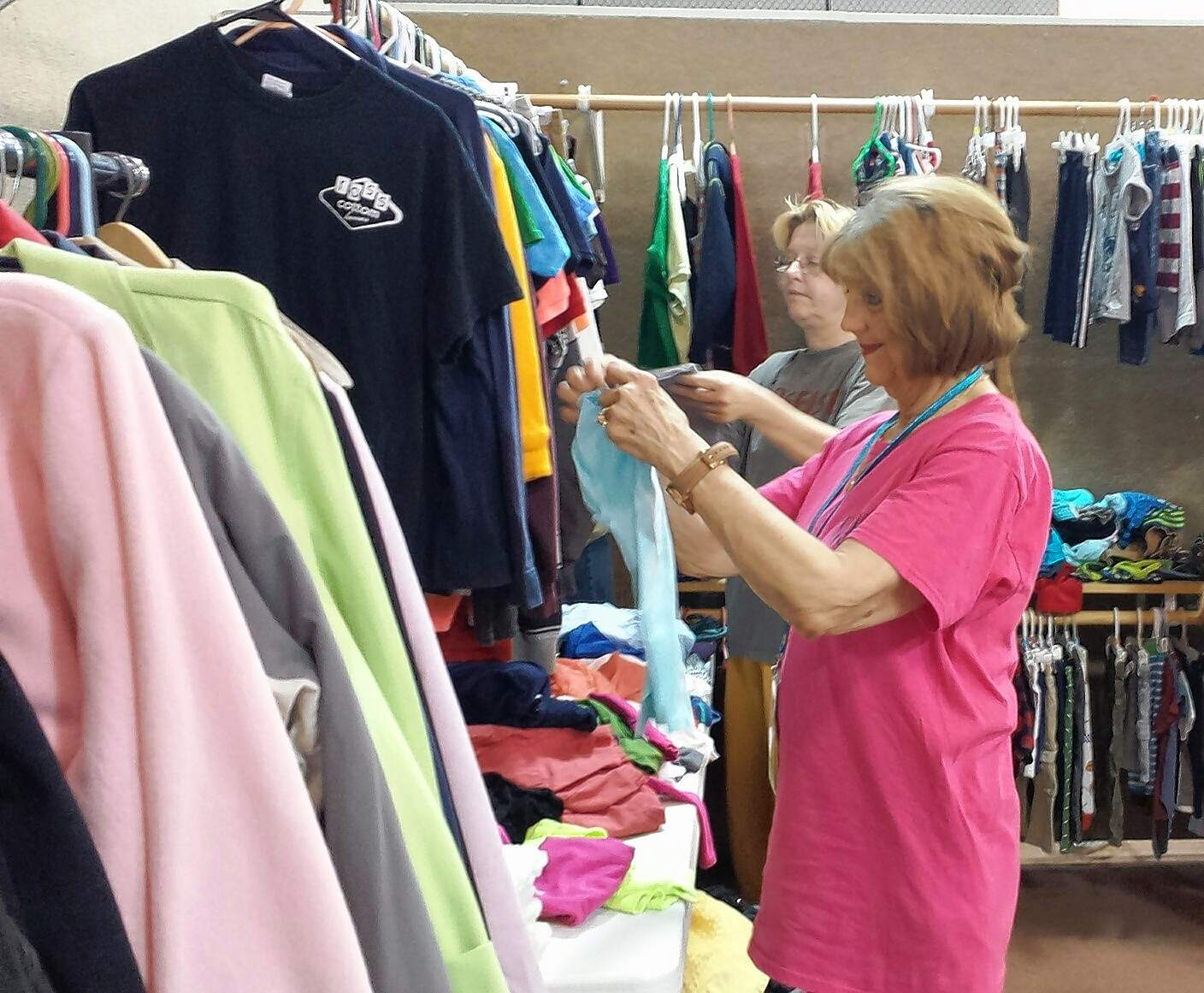 Volunteers Linda Teegarden, foreground, and Sheila Mann sort clothing to put on hangers Tuesday morning prior to the opening.
