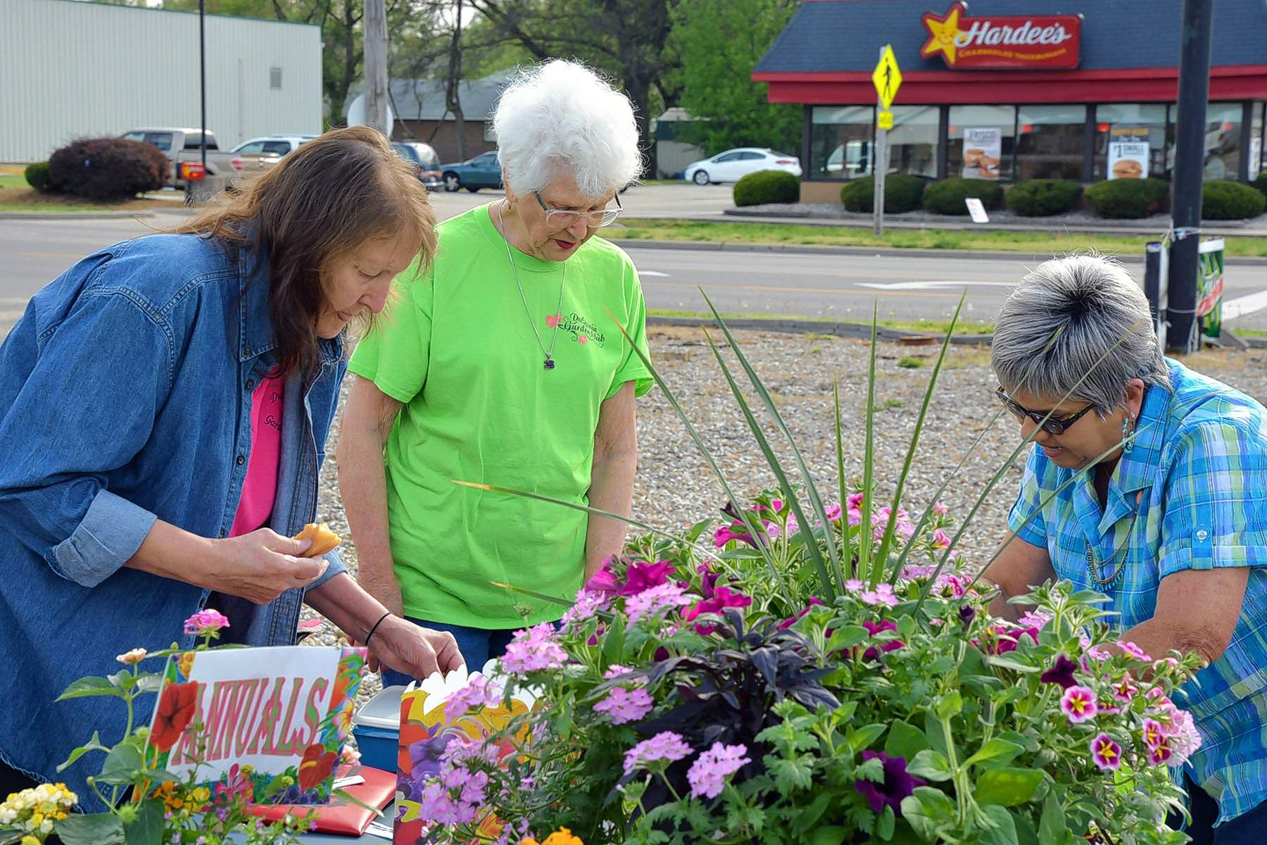 Du Quoin Garden club members Connie Galloway and Verna Bastien help Shirley Weasel with plant selections Saturday.