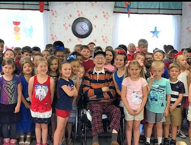 "Gilbert Ledbetter, center, gets a visit from a group of schoolchildren who sing ""God Bless the USA."""