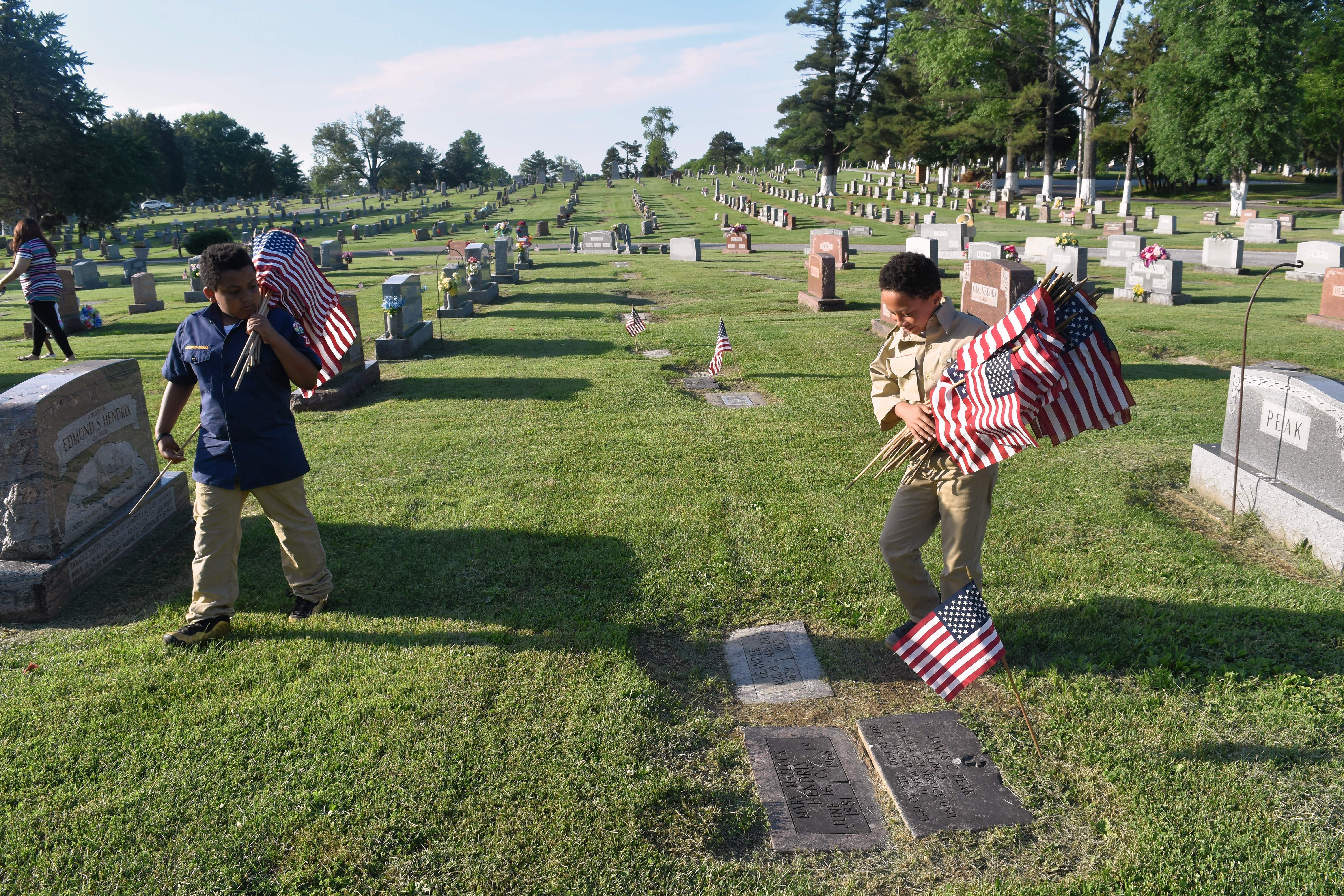 Bear Scout Isaiah Taborn, left, and Webelos Scout Donovan Stewart place flags near veterans' grave markers Wednesday evening at Sunset Lawn Cemetery in Harrisburg.