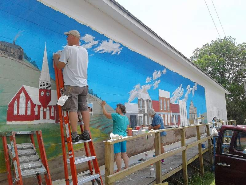 Historical society members work on a mural along the side of their building on Main Cross Street in Galatia.