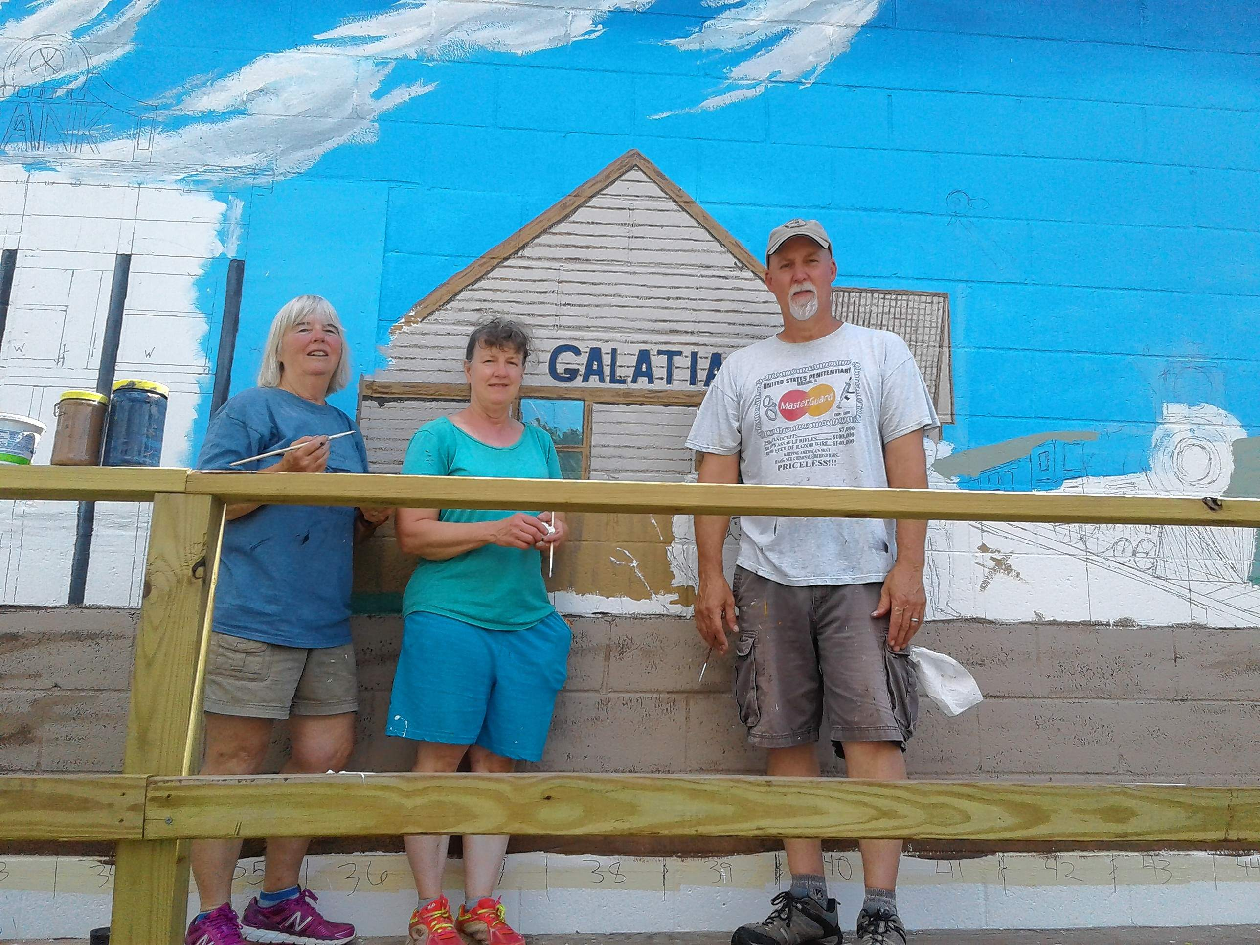 From left, Janet Bixler, Missy Carstens and Kris Killman stand with a portion of the mural they are painting on Main Cross Street in Galatia, which should be done in time for Old Settlers Days this weekend.