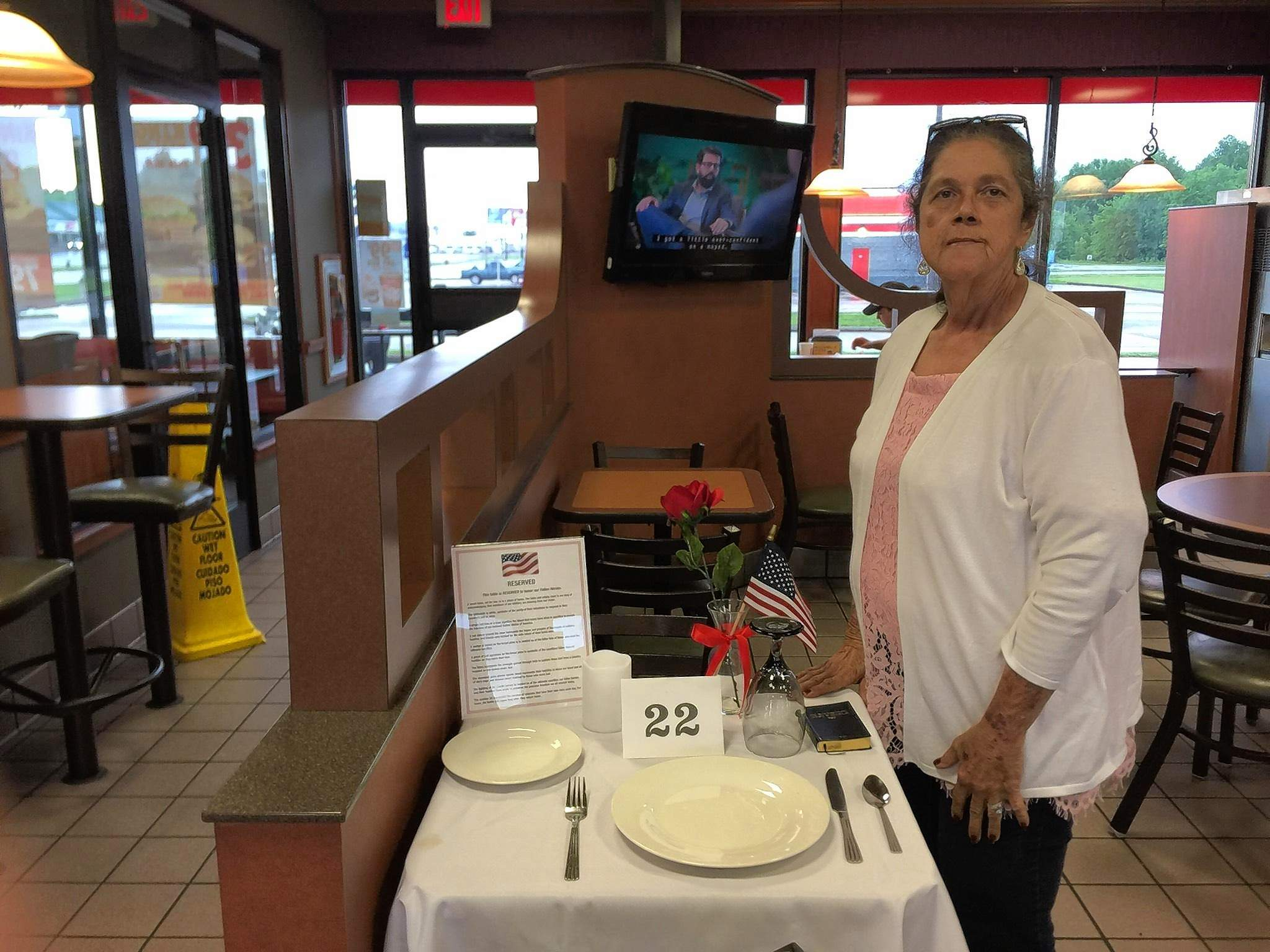 Mary Rivera, a member of the Michael Hillegas DAR, stands with reverence beside the Missing Man Table set up for Memorial Day at Burger King. The table is a place of honor, set up in memory of fallen, missing, or imprisoned military service members.