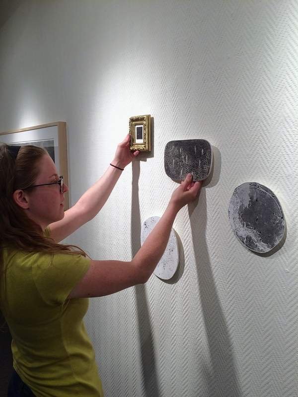 """Artist Emily Elliott, a Philadelphia-based artist and SIC graduate, hangs a selection of works at the SIC Art Gallery Tuesday morning. The exhibition, called """"Nightwalks,"""" opens Wednesday, with a reception at 7 p.m. Friday at the gallery."""