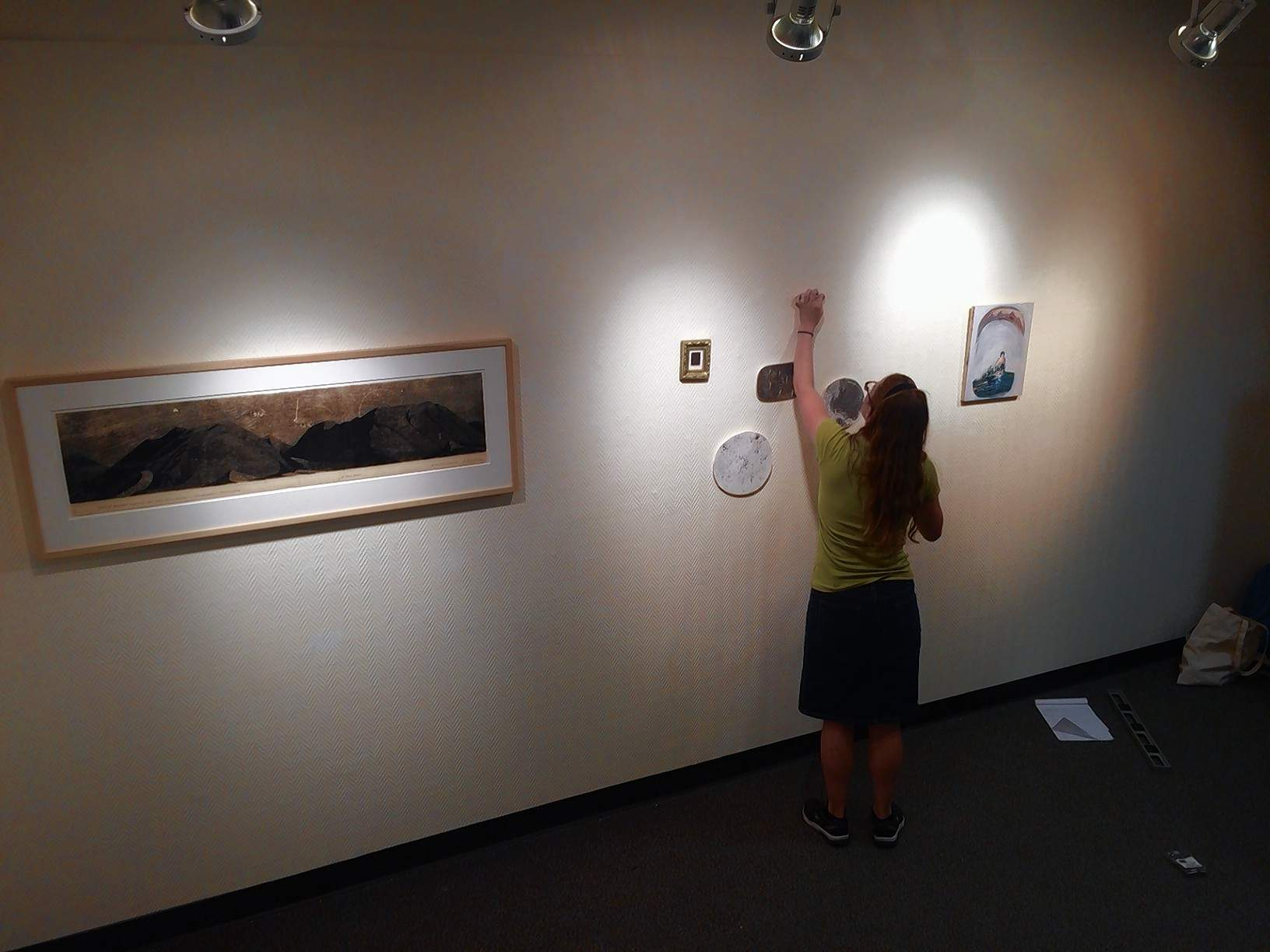 "Artist Emily Elliott, a Philadelphia-based artist and SIC graduate, hangs a selection of works at the SIC Art Gallery Tuesday morning. The exhibition, called ""Nightwalks,"" opens Wednesday, with a reception at 7 p.m. Friday at the gallery."