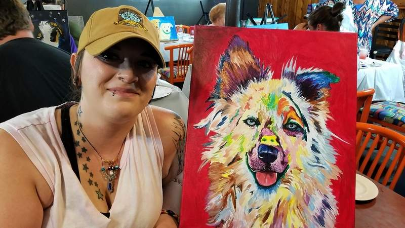 Bar manager Cadey Hess poses with her artwork.