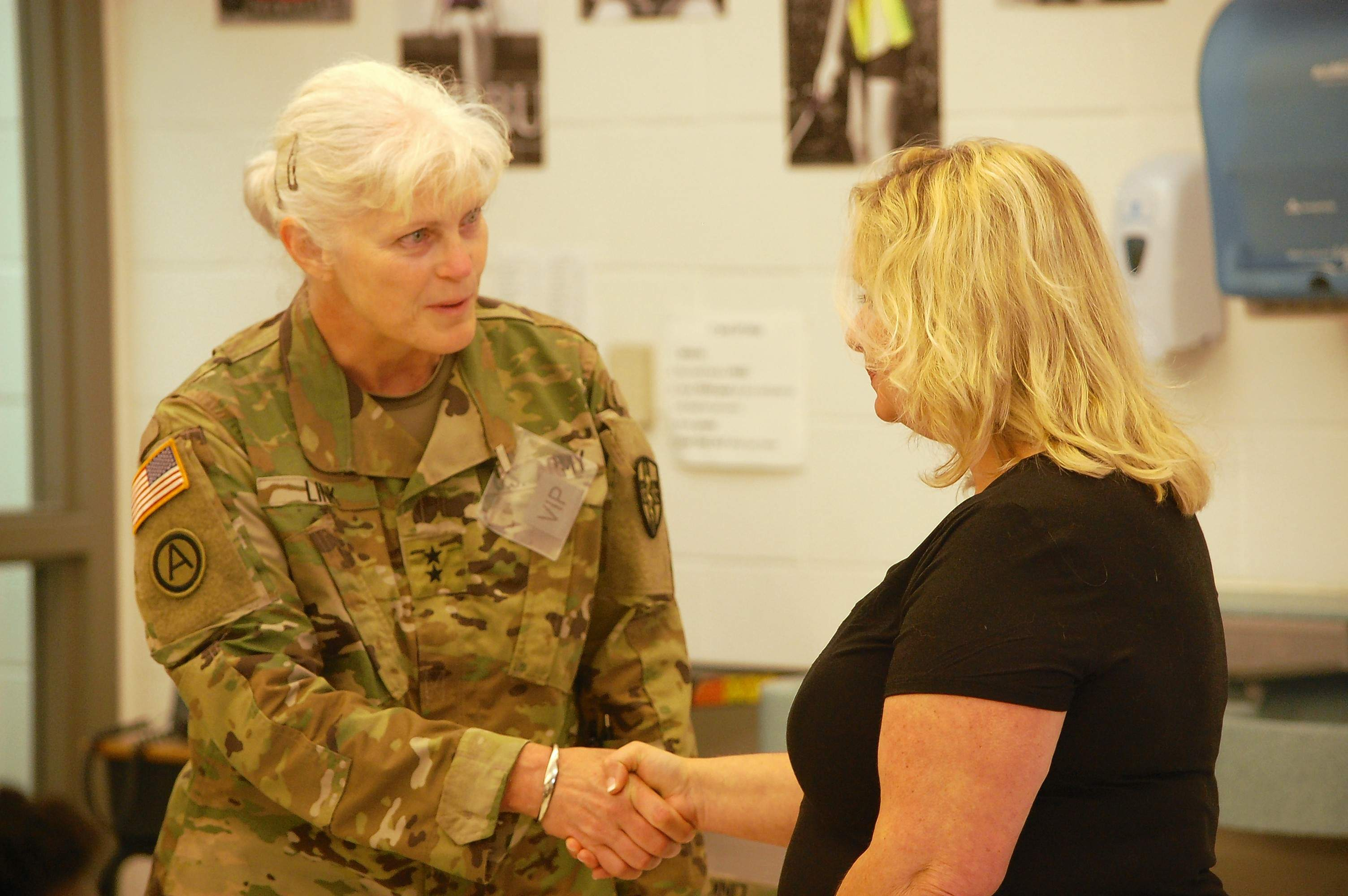 Major General Mary Link, Army Reserve Medical Command commanding general, presents Kim Watson with a medallion for her service to the Southern Care Innovative Readiness Training healthcare mission underway at Harrisburg Middle School. Watson, of Harrisburg, is a senior account manager for the Illinois Department of Commerce and Economic Opportunity.