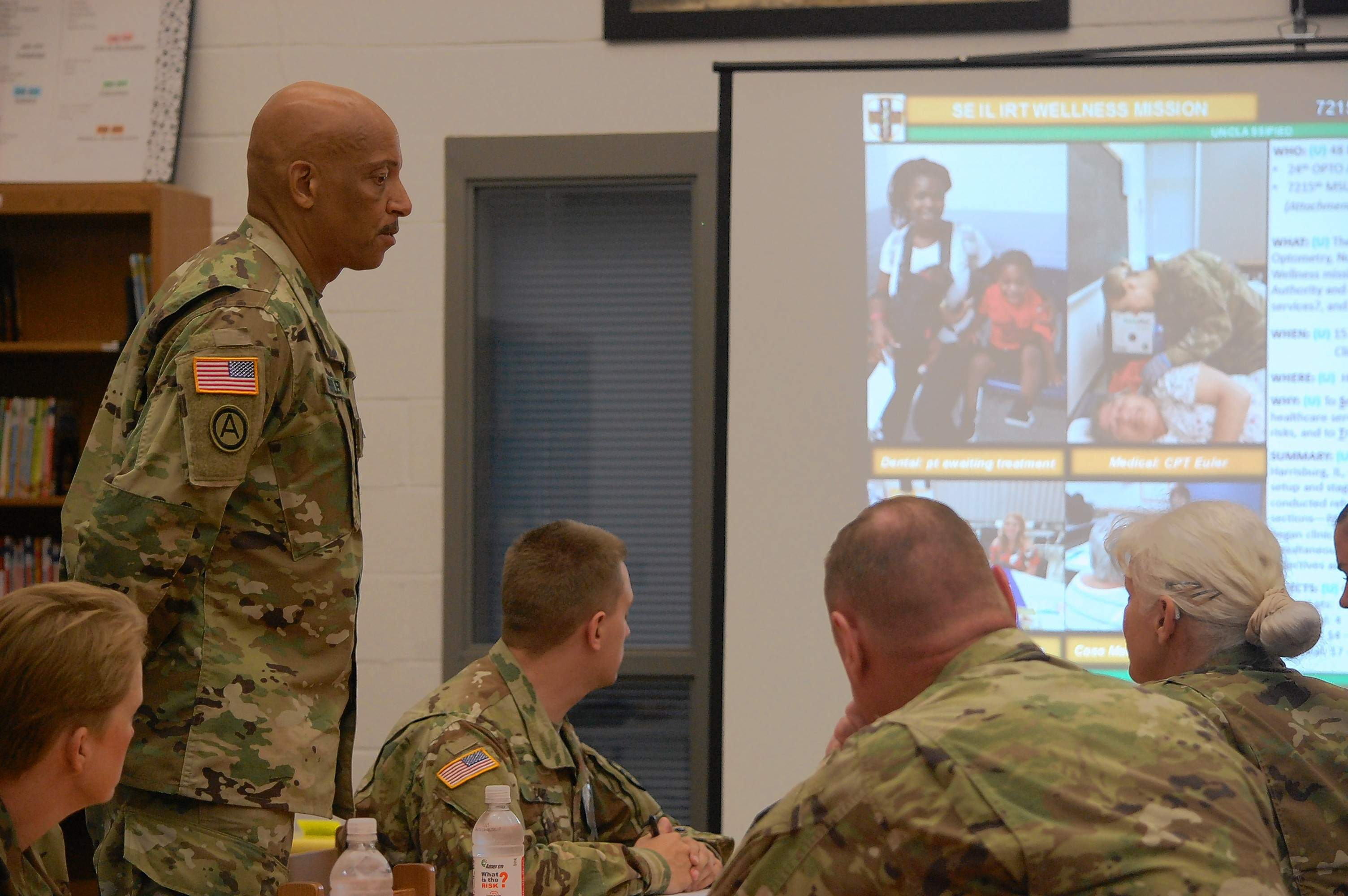 Lt. Col. Milton Fowler, standing, left, observes as service members are briefed on the healthcare screening mission.
