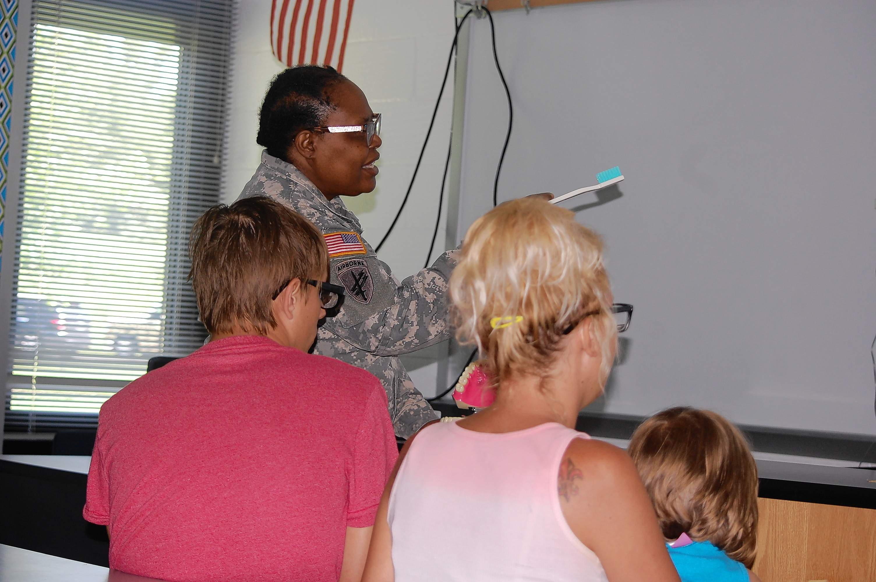 Staff Sgt. Estella Brown-James demonstrates oral hygiene with an oversized toothbrush. Amy Smith of Harrisburg, and her son, Josh Smith, listen.