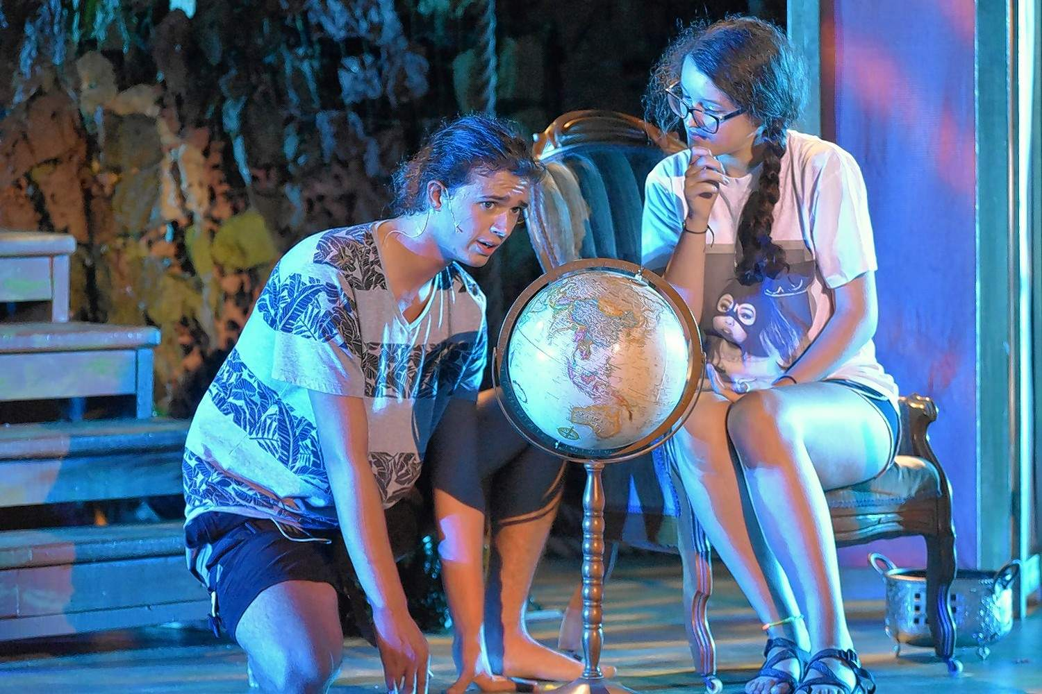 """Tarzan, played by Levi Titsworth, looks at a globe under the direction of Jane Porter, played by Alyssa Irvin. """"Tarzan: The Stage Musical"""" starts today at Southeastern Illinois College."""