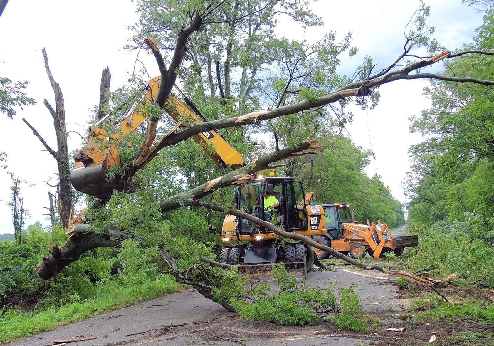 Greg Cowger, maintenance worker for the Saline County Highway Department operates an excavator to move a large tree which fell across Tuller Road during a storm Tuesday evening near Carrier Mills. Fellow worker, Brian Leibenguth, assists on the backhoe in the background.