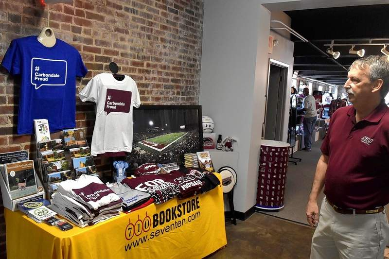 Randy Johnson, co-owner of 710 Bookstore, looks over some of the T-shirts emblazoned with the Carbondale Proud logo at the store's new location on South Wall Street.