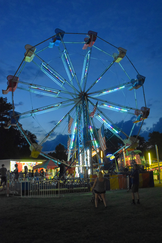 TRAVIS DENEAL PHOTOThe Ferris wheel lights up as it spins at the Saline County Fair Saturday night.