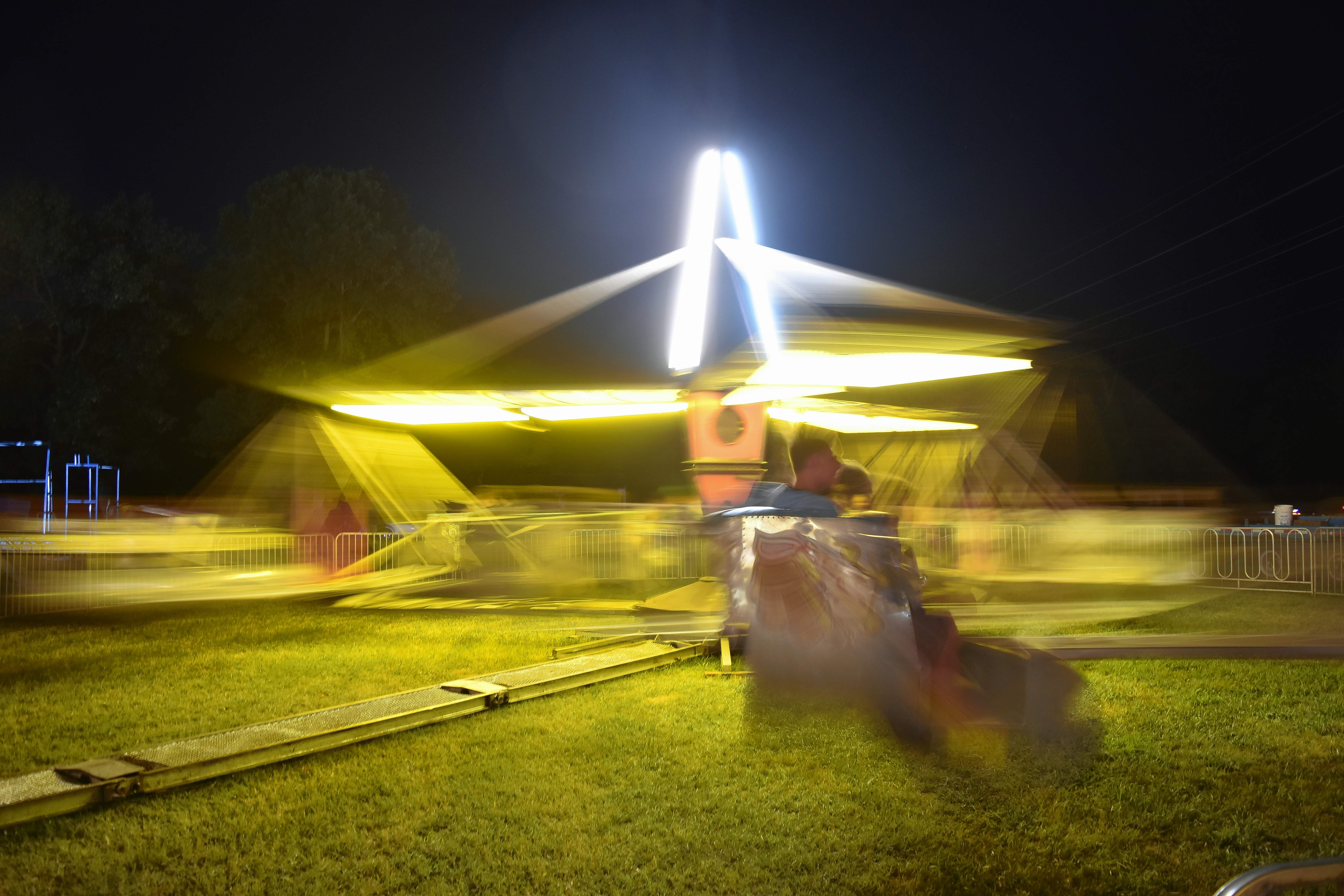 TRAVIS DENEAL PHOTORiders on the Scrambler are a blur as the fair ride rapidly spins.