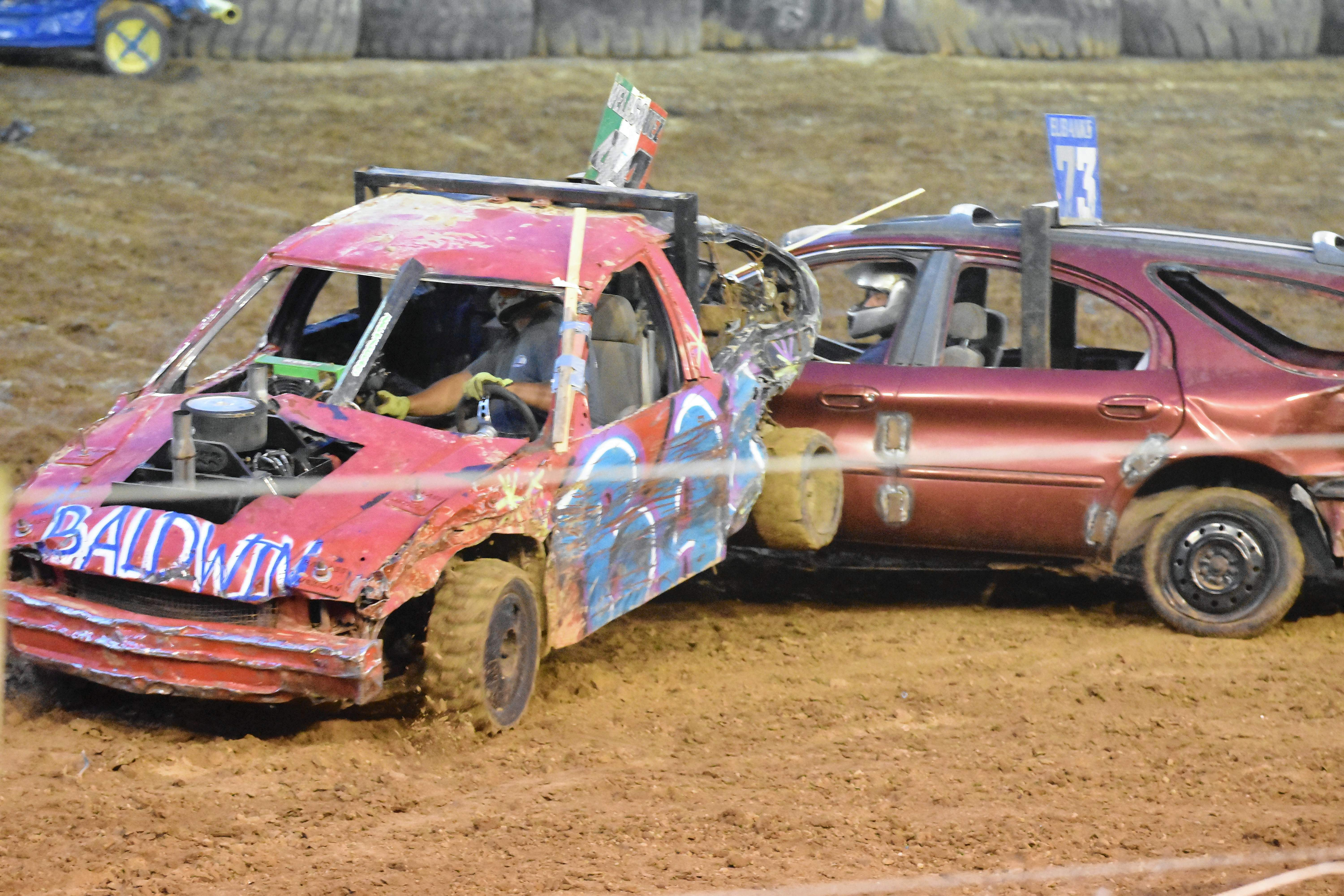 "A car rides its rear end up on a competitor during the ""mini car"" segment of the demolition derby Saturday night."