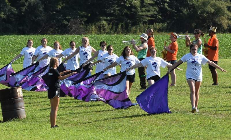The color guard performs, as marching band members play and drum majorette Sophie Winkleman directs Friday afternoon near the end of marching band summer camp.