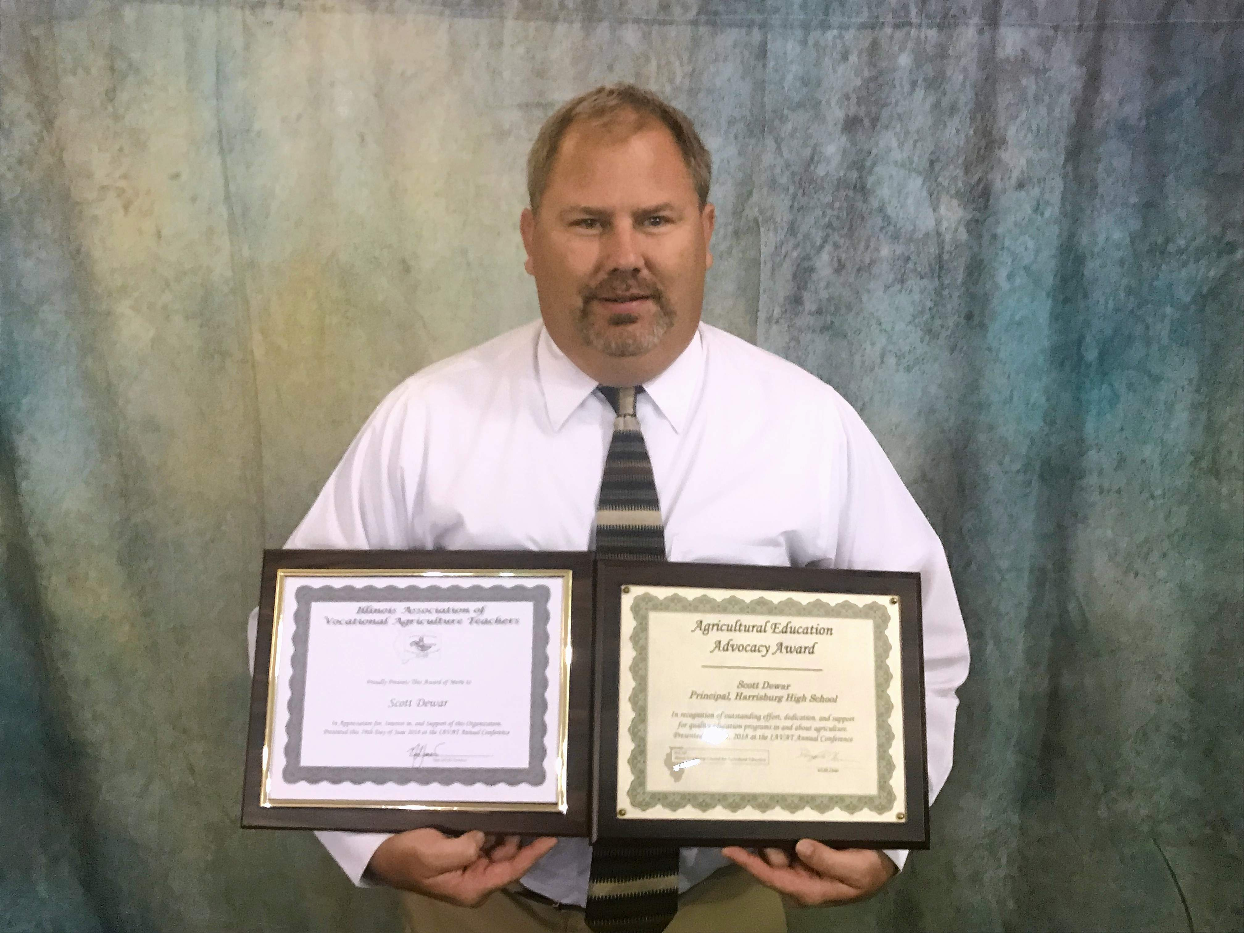 Harrisburg High School Principal Scott Dewar, holding his FFA District V Agriculture Education Advocacy Award certificates. The award recognizes Dewar's extensive support of the HHS FFA program.