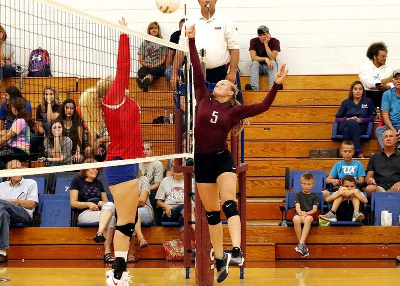 Sesser-Valier/Waltonville's Mikayla Robbers (right) hits the ball across the net in match action with Woodlawn last week.