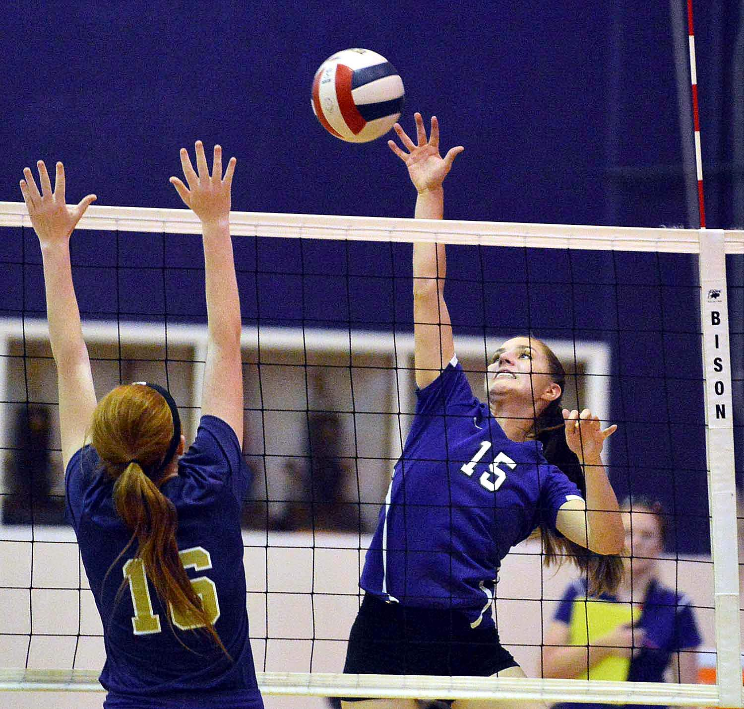 Harrisburg's Madeline Rider drives the ball over the net and outstretched hands of Eldorado's Briley Lenkatis.