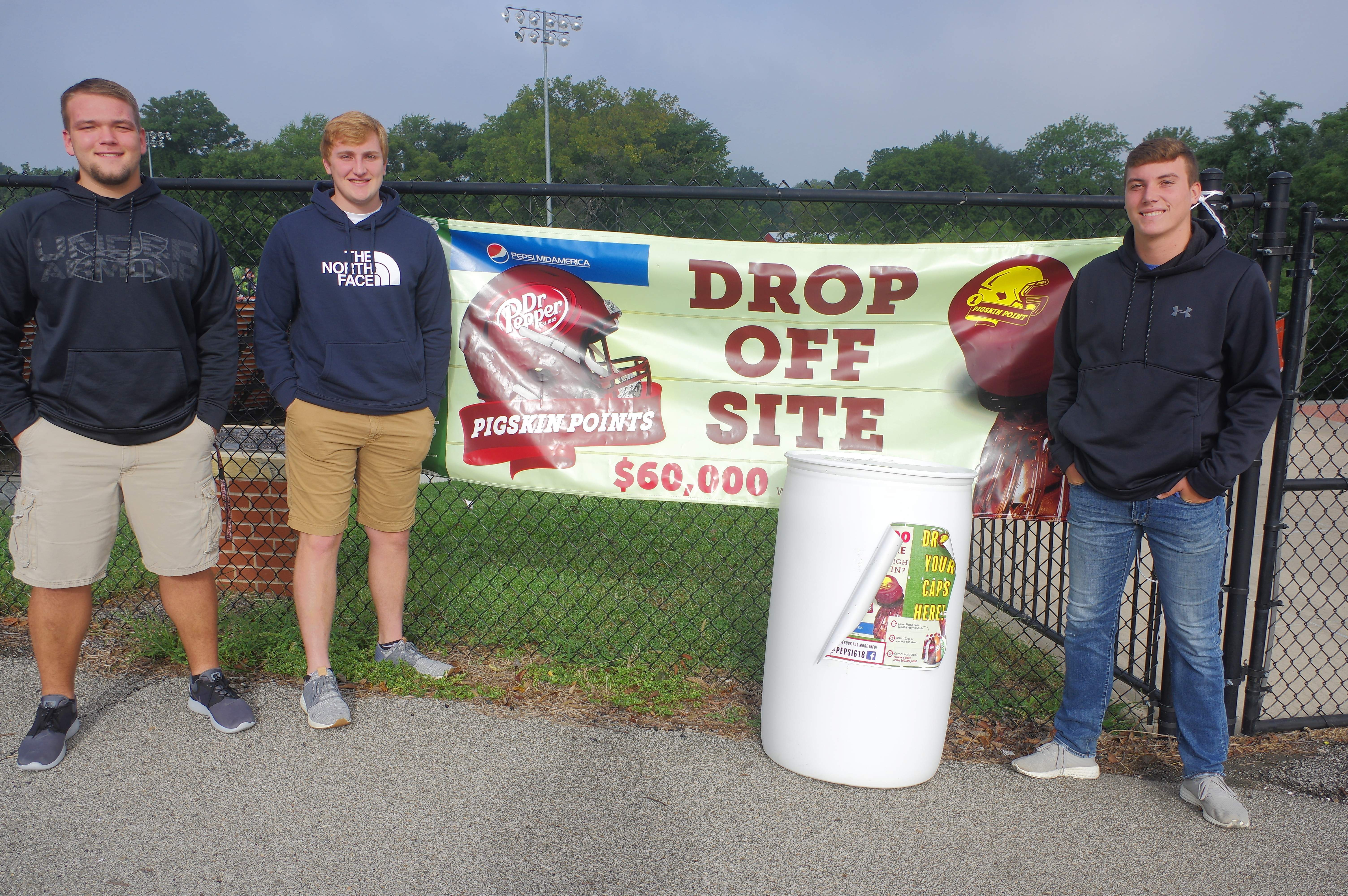 Chester High School Football players, from left, Chase Colvis, Drake Bollman and Nick Meyer stand by the collection barrel for the 2018 Pepsi MidAmerica Pigskin Points contest at the entrance to W.O. Smith Field, in which Chester High School is competing.