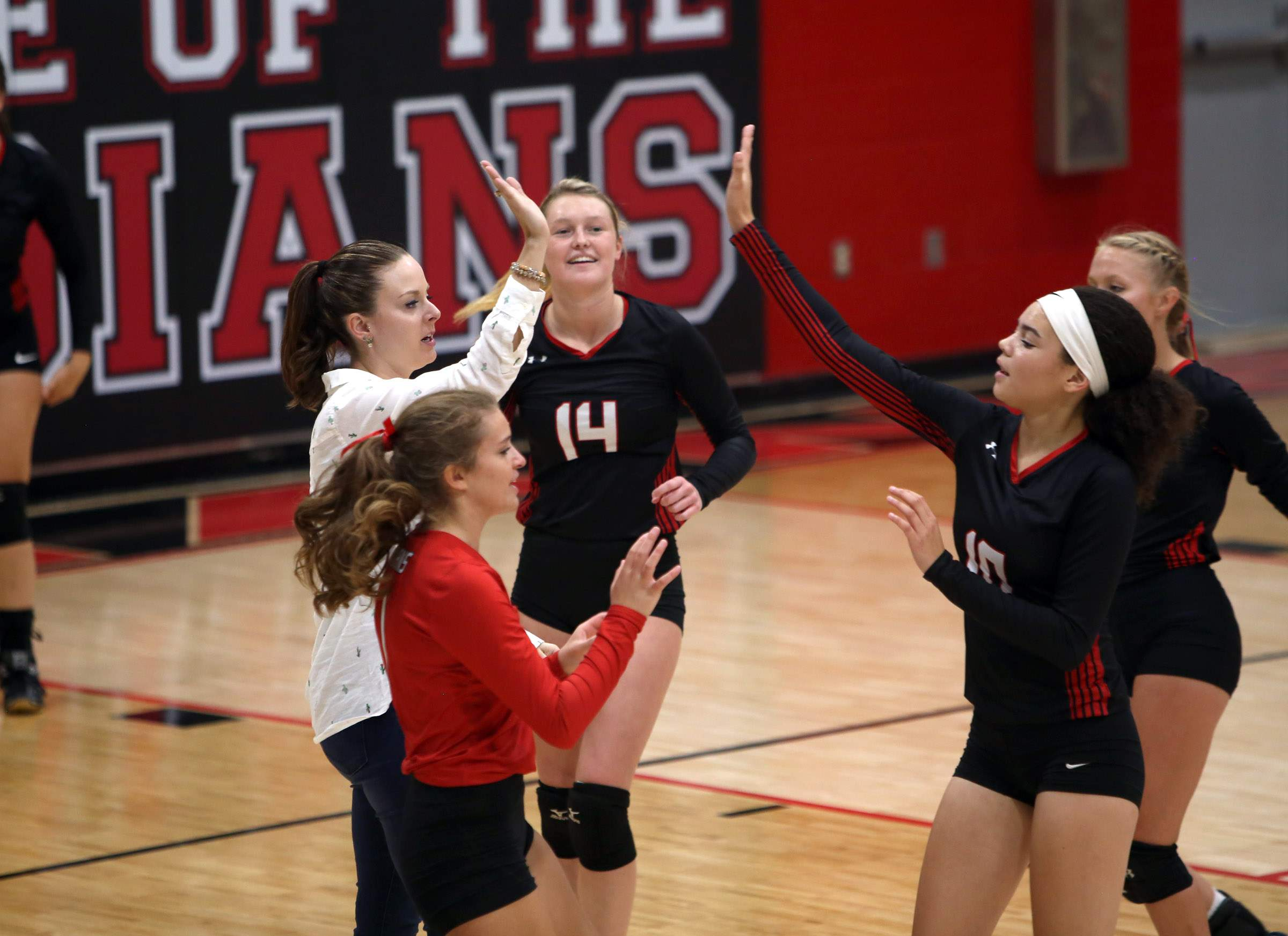 Johnston City coach Ashleigh Reeves gives a high five to Alexis Turner with Reilly Baker (14) and libero Gia Ordonez nearby Wednesday night.