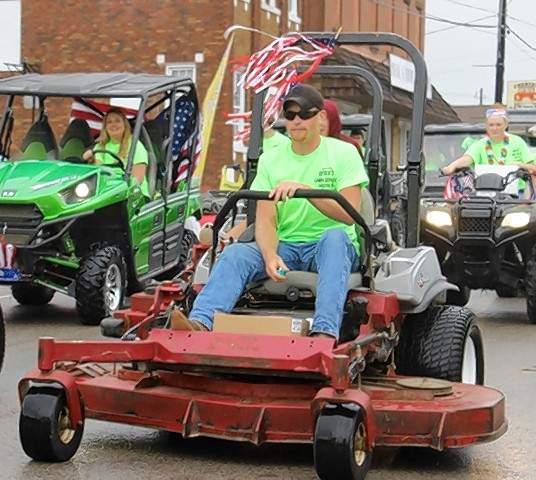 Derek Niermann of Derek's Lawn Service leads an entourage at the 39th Annual Popeye Picnic parade.