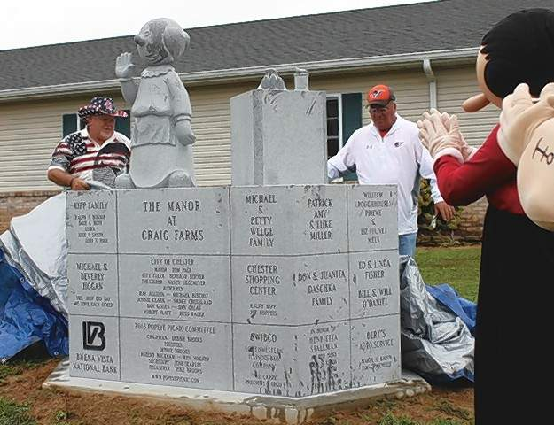 The newest character on the Popeye Character Trail -- Nana Oyl -- is unveiled at the Manor of Craig Farms by Stan Newby, maintenance supervisor at the Manor, and Chester Mayor Tom Page.