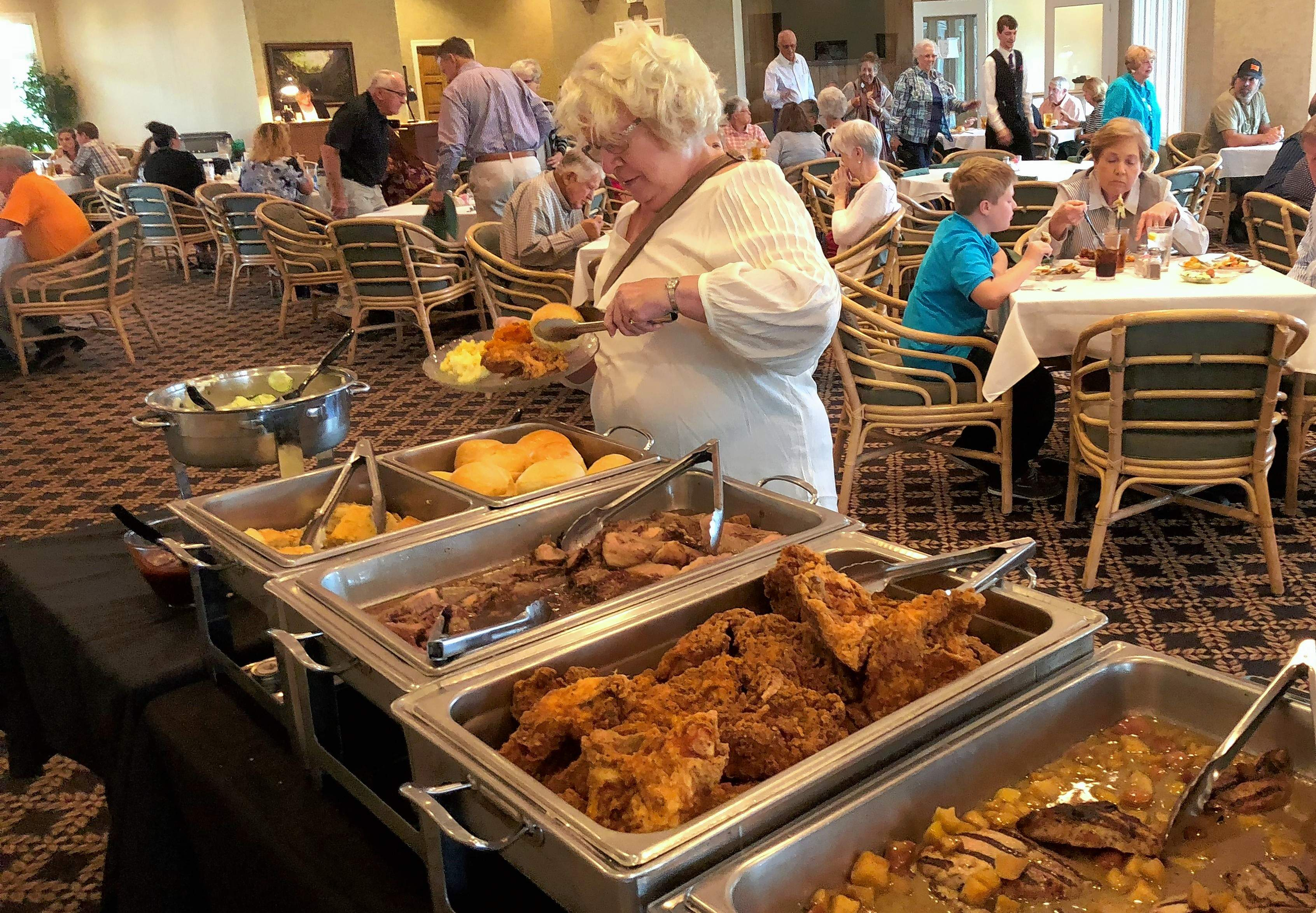"Jo Davis fills her plate in the buffet line during Saturday's ""Farmers Market Buffet"" at Marion's Kokopelli Golf Club."