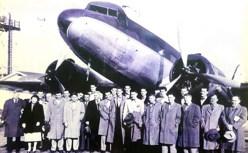 Jim Vest (fourth from right), a sophomore guard on the Western Kentucky basketball team, poses with his teammates outside the airplane that transported the 1952 Hilltoppers team to New York to compete in the National Invitational Tournament (NIT), where the team reached the semifinals.