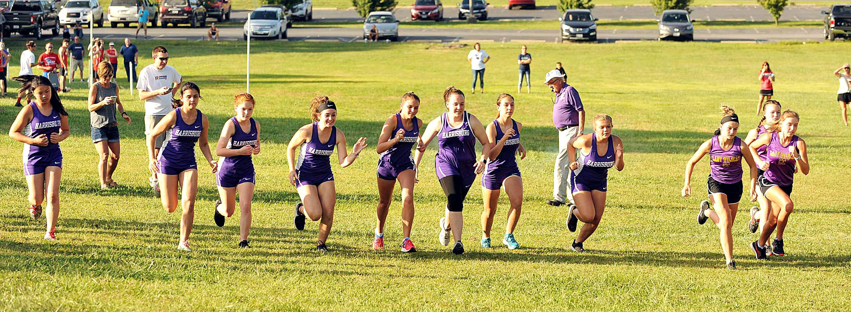 From left Harrisburg cross country runners Selina Wang, Sierra Winstead, Emily Jeffries, Hannah Reid, Shaunah Ballard, Claire McDermott, Maddie Johnson and Ashley Hurst join Carrier Mills-Stonefort runners at the start of Tuesday's Harrisburg Invitational at SIC.