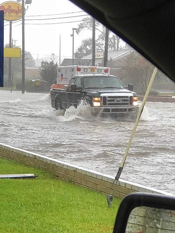 A truck and ambulance navigate the flooded streets of Dillon, South Carolina, on Sunday.