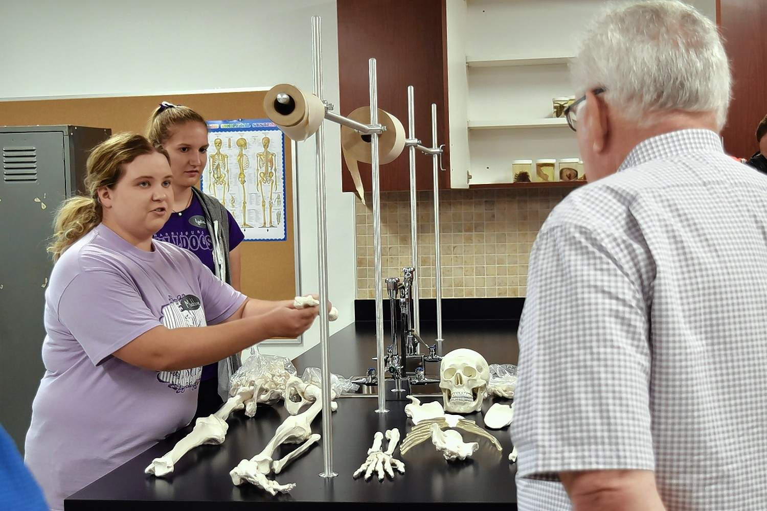Juniors Madeleine DeNeal, left, and Lydia Miller give a demonstration about bones of the body with a new replica skeleton purchased with money donated by Paul Jones, right.