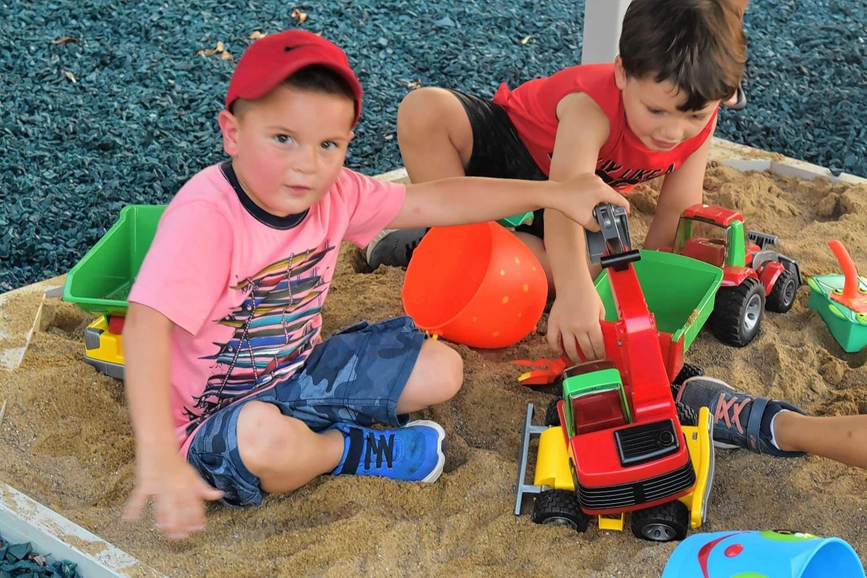 Bryar Black, left, plays in a sandbox underneath some of Eldorado Grade School's new prekindergarten playground equipment.
