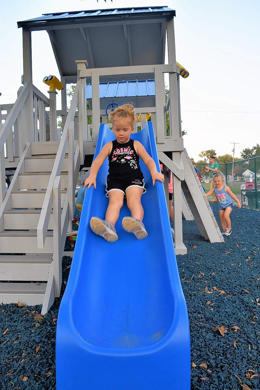 Kayla Wagenblast slides down a new slide at the Eldorado Grade School Thursday evening.